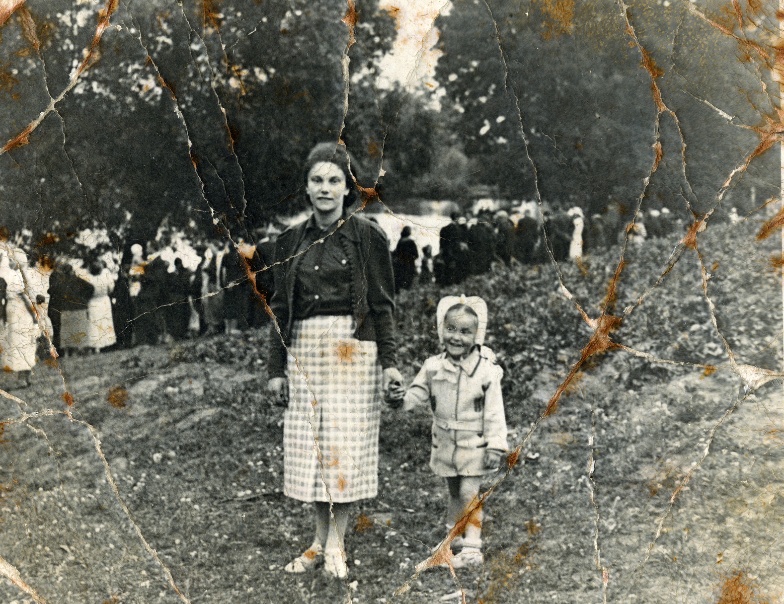 Musia and Leah Szklut stand in front of a river in Naliboki [possibly to do tashlich -- the ceremonial casting of sins performed on Rosh Hashana].  The mother and child were both killed during the Holocaust.