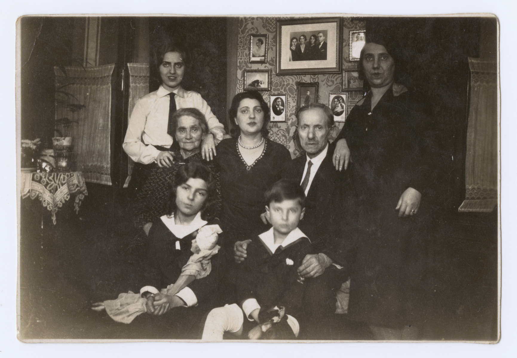 The extended Schwarz family poses for a group portrait in their home.    Marta Koranyi is at the bottom left; her brother Erwin is at the bottom right.  Also pictured are her parents, Sigmond and Sara (nee Schwarz) Koranyi ,and grandparents.  her maternal aunt is at the top right.