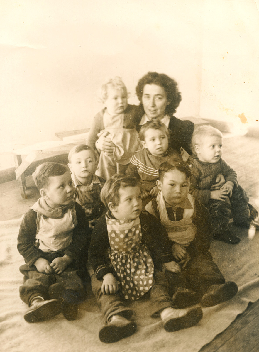 Leah Laufer holds Elana Millman in her arms surronded by other young children in the Bergen Belsen displaced persons camp.  Leah Laufer was a representative of the Zionist youth movement Hashomer Hatzair that organized the Youth Aliya transport that brought Elana to Israel.