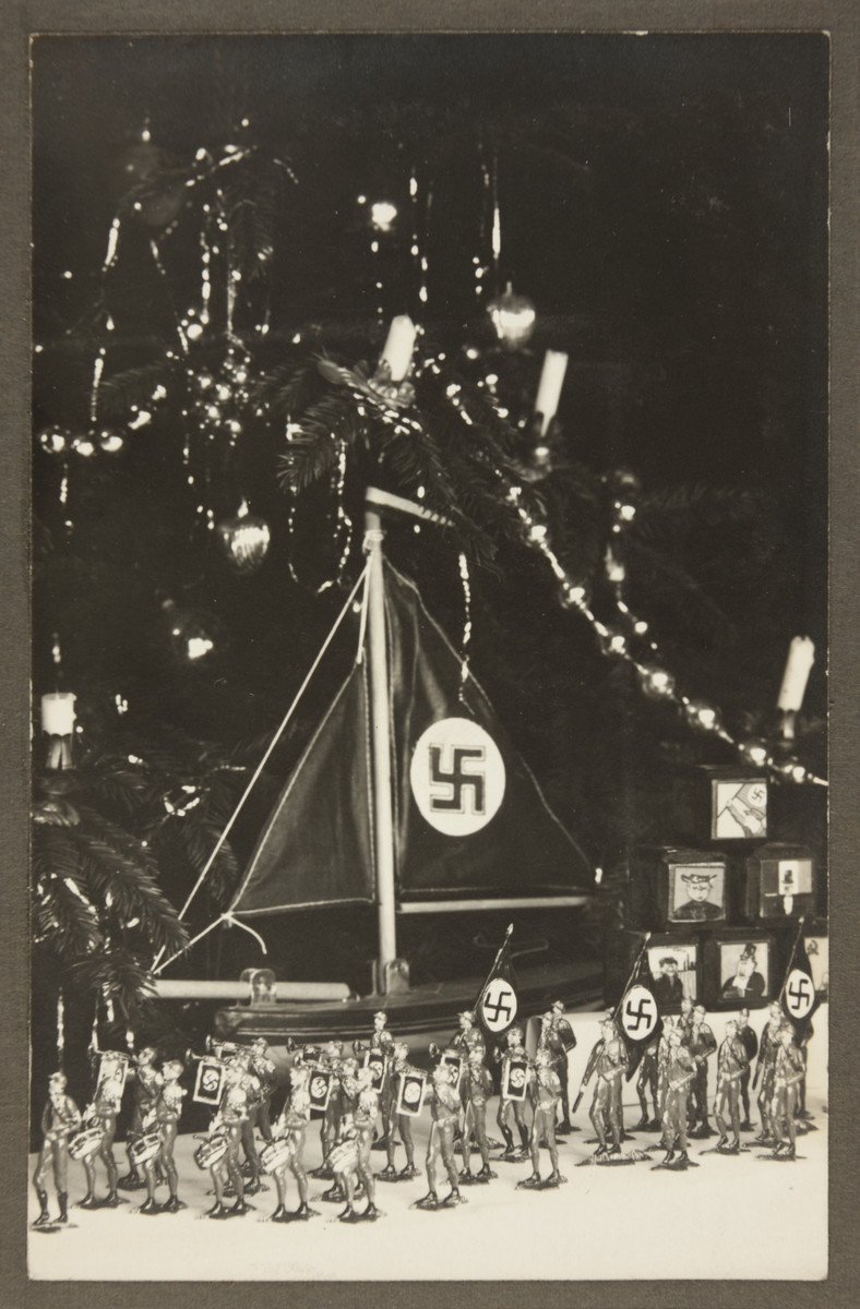 Children's toys, including tin Nazi stormtroopers and a toy ship with a Nazi flag are displayed before a Christmas tree.