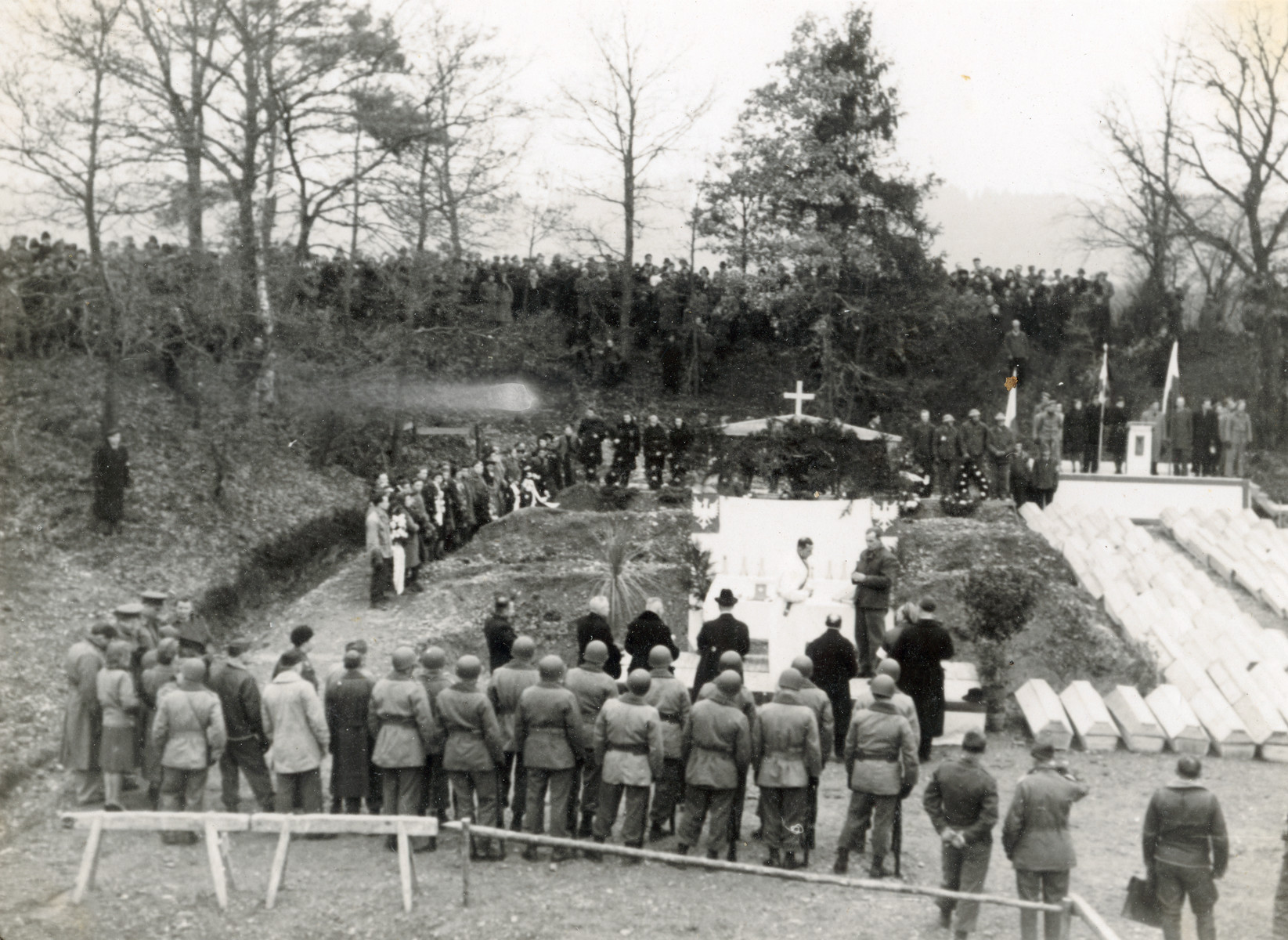 A priest conducts a service during the exhumation and reburial of Christian victims of the Pocking concentration camp attended by survivors and American soldiers.