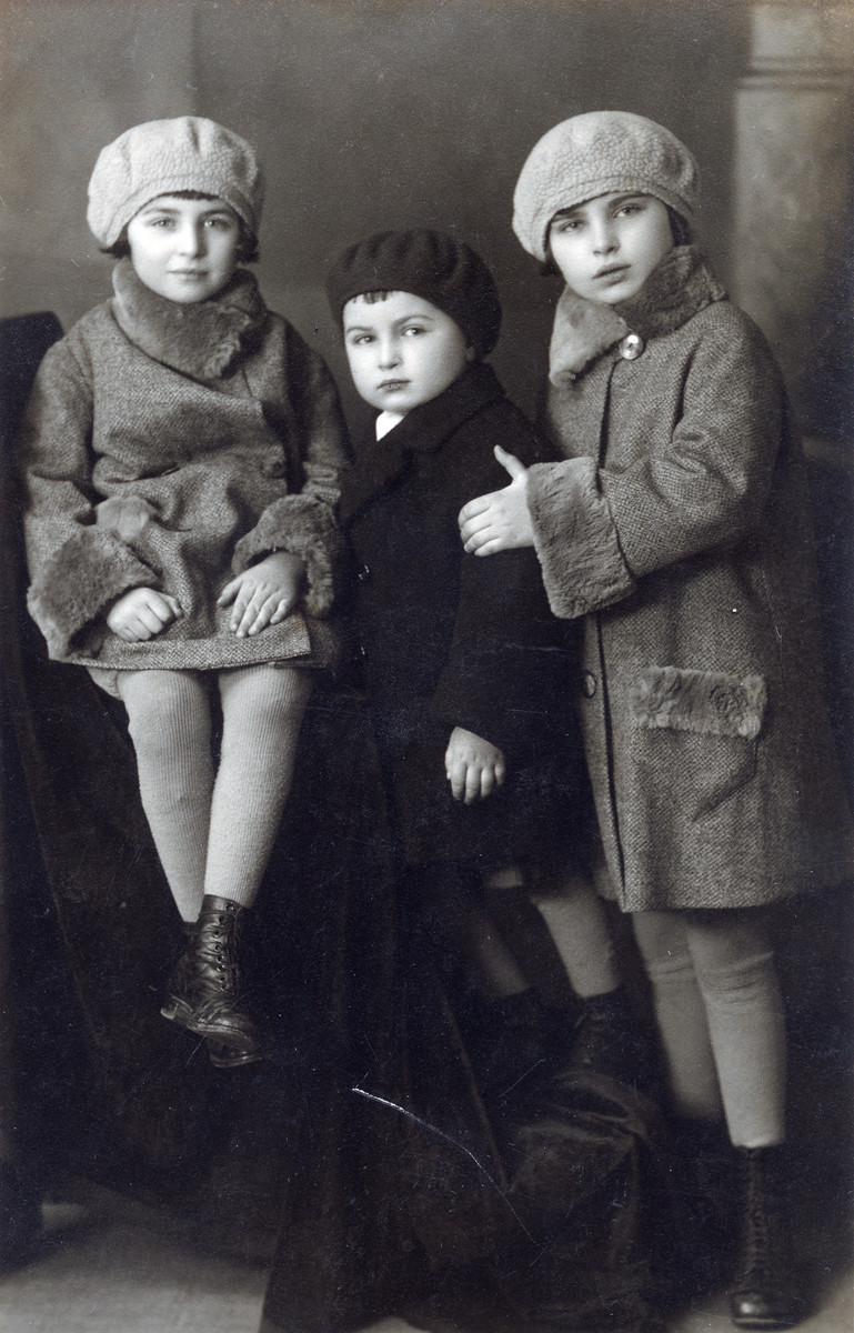 Hana (left) and her sister Irena (right) pose for a studio portrait with an unidentified child wearing coats sewn by a relative.