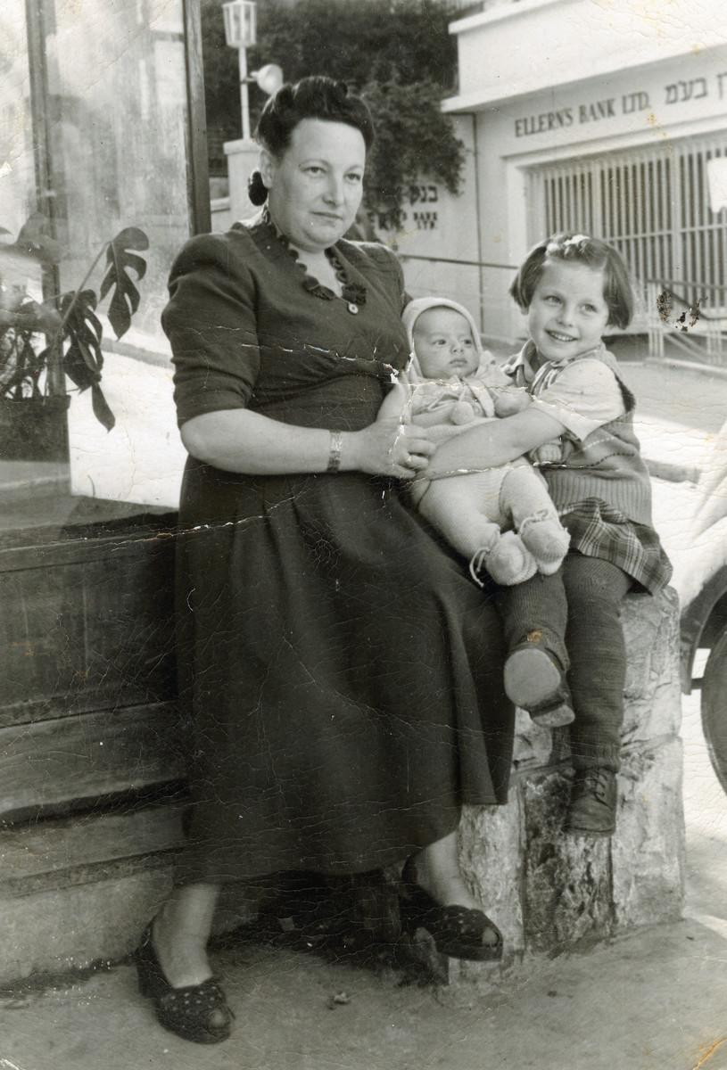 Elana Millman's biological mother Franka, her sister Danuka and half-brother Michael rest outside a bank in Haifa.