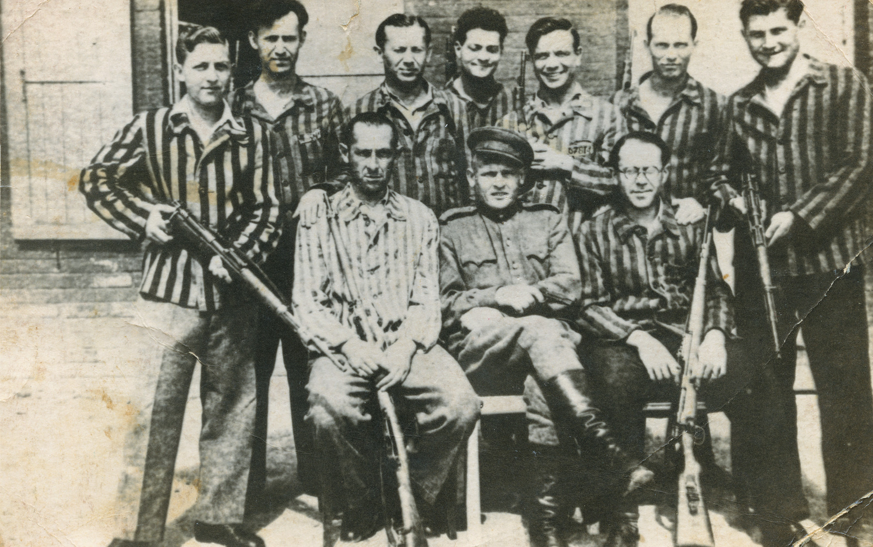 Group portrait of a Soviet soldier and liberated prisoners, some holding weapons, in the Buchenwald concentration camp.  Henrich Drabinowski on the left holding a rifle.