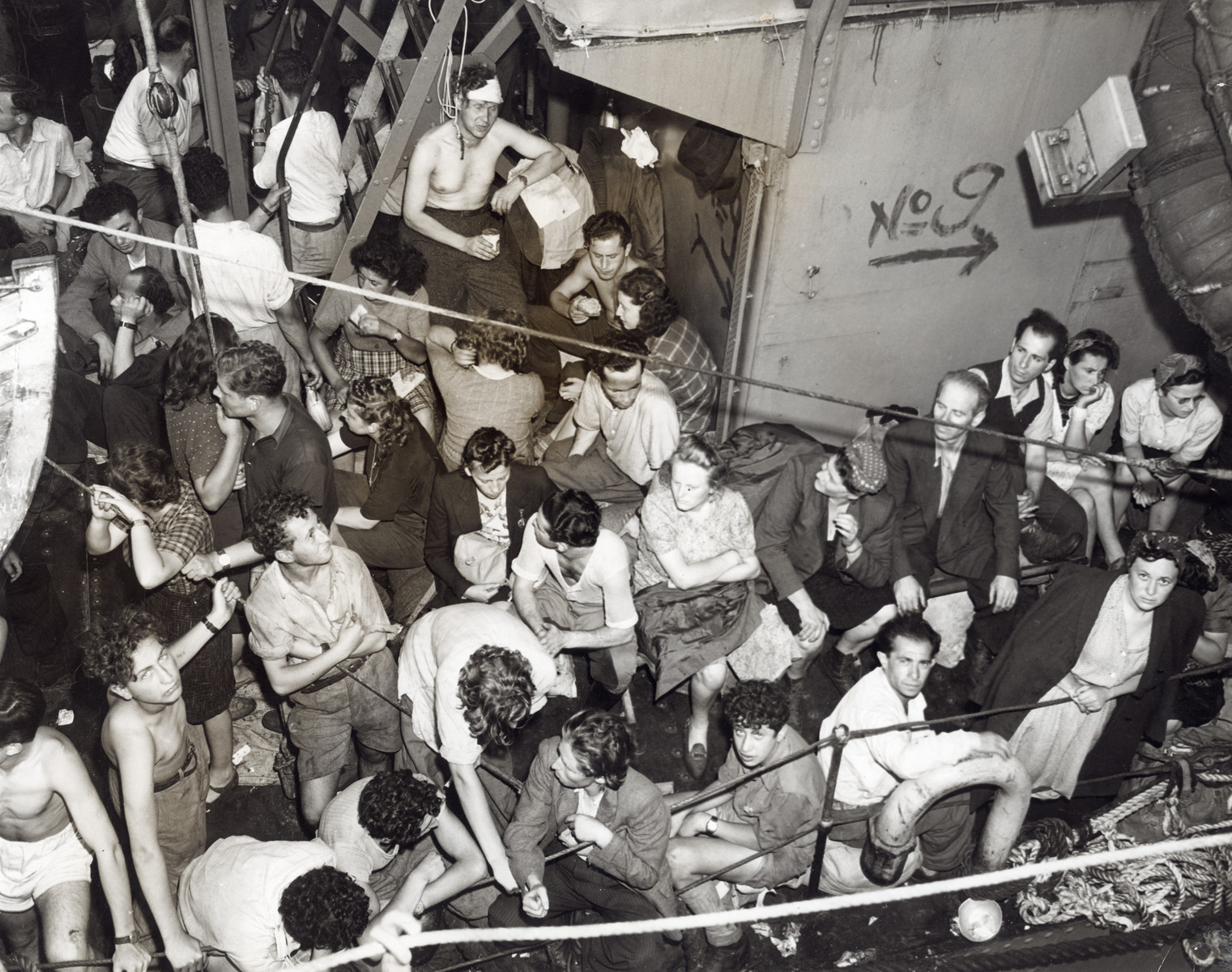 """Refugee Jews wait aboard the Josiah Wedgewood after the British navy fired at ship  The original caption reads: """"The former Canadian corvette Josiah Wedgewood, with 1,300 European Jewish refugees aboard, was captured near here June 27th by British warships after a dramatic attempt to escape authorities and land illegally in Palestine. The refugees, many of whom has spent years in German concentration camps, did not halt their ship until three warning shots were fired from the HMS Haydon, a Bristish Destroyer. Sailing under Panamanian registry, the corvette was spotted seventy-three miles out at sea by aircraft, but the British could not act until attempt was made to enter territorial waters. The Jews were detained at Athlit Clearance camp on the official charge of being a """"menace to navigation."""""""""""
