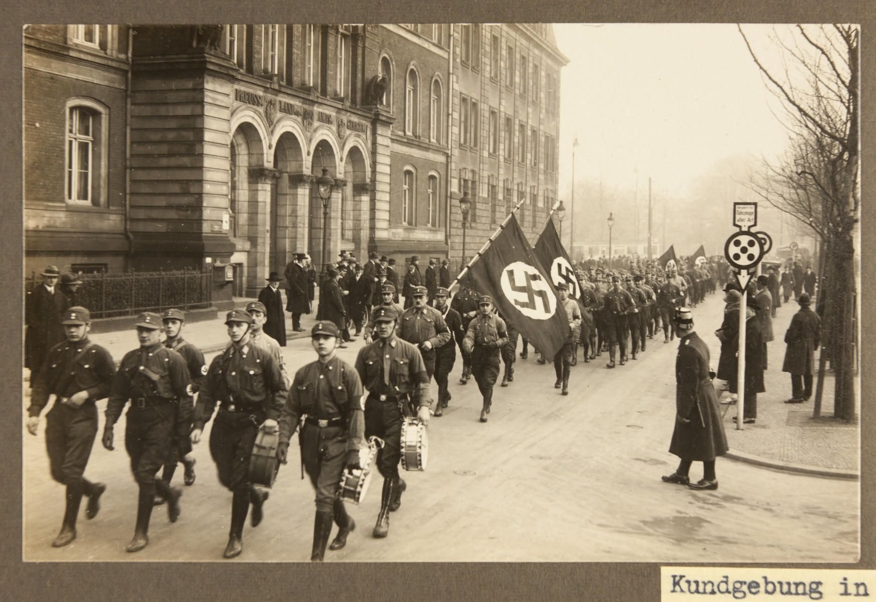 Uniformed SA men parade down a city street in Duisburg during a Nazi rally.