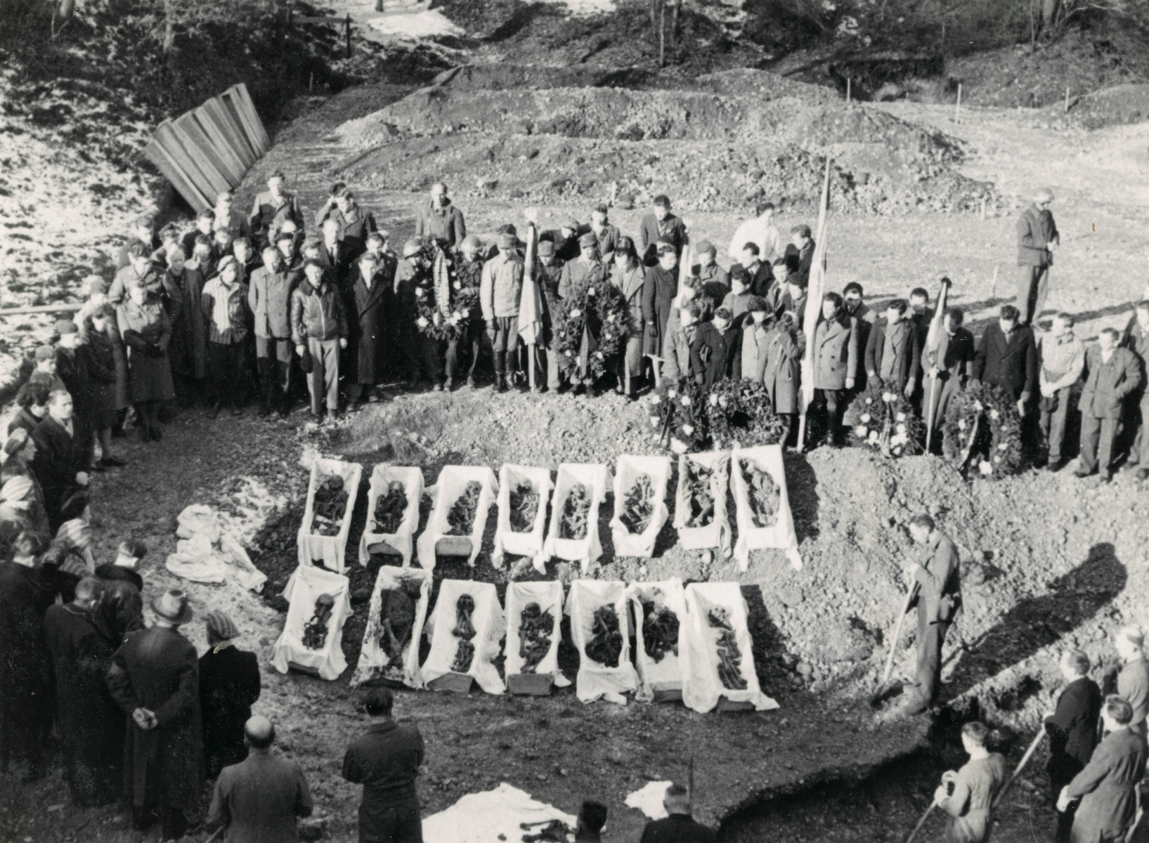 Survivors gather by exhumed bodies of those who  perished at the Pocking concentraion camp before the monument to the victims was created.