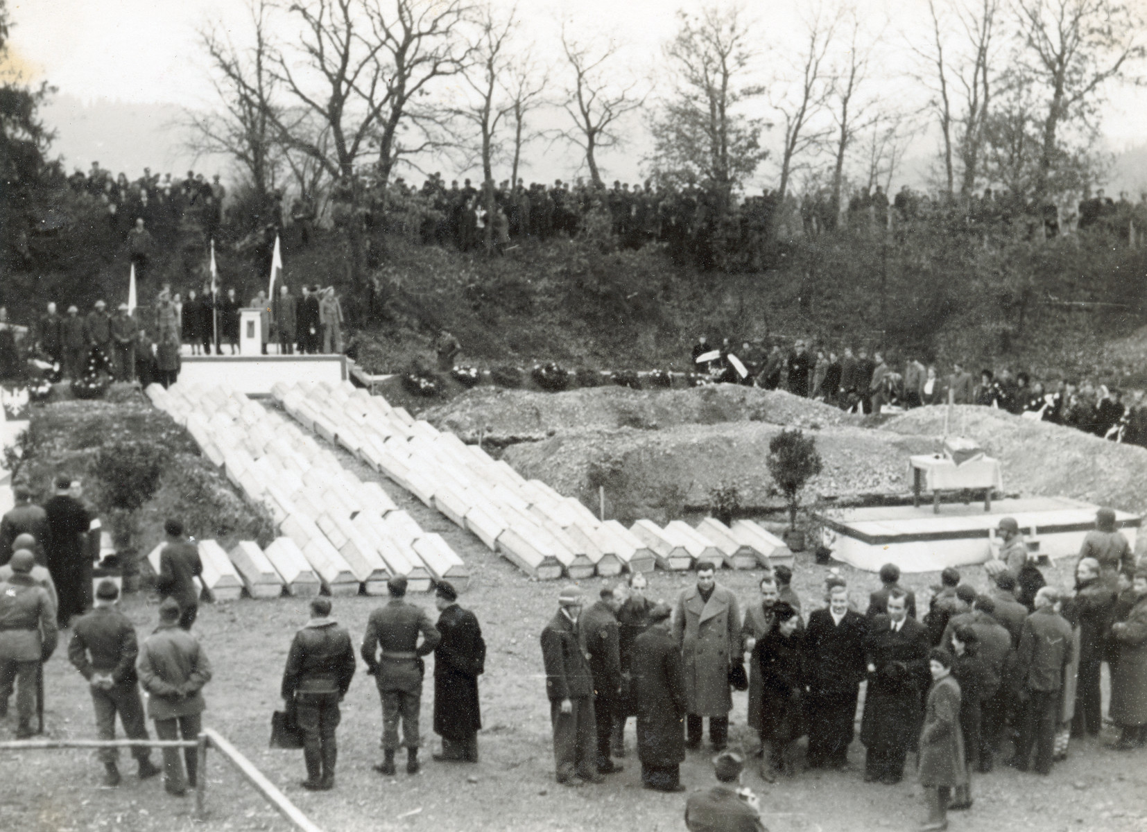 Survivors and American soldiers attend an exhumation and reburial ceremony of the victims of the Pocking concentration camp.