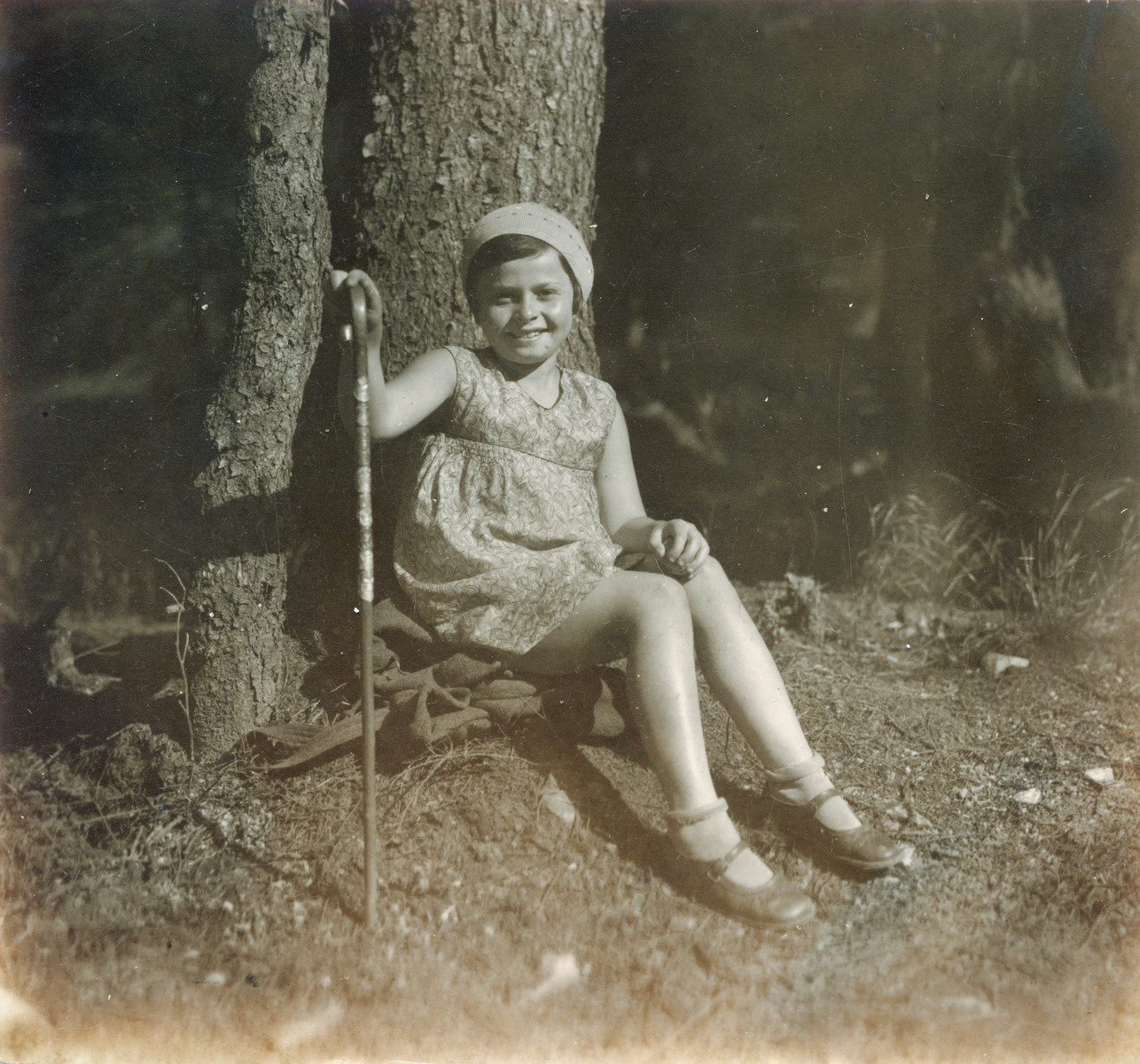 Hana Lustig rests under a large tree during a hike.