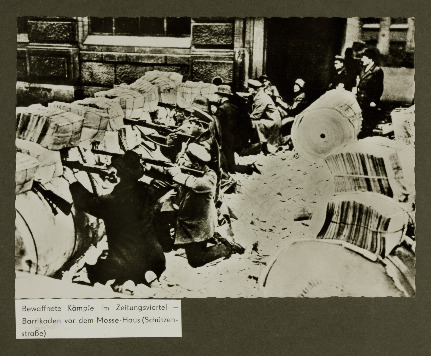 """Armed Spartacists barricaded behind stacks of newspapers during the Spartacist Uprising.  The text reads: """"Armed clashes in the newspaper quarter. Barricades in front of the Mosse - Haus (Schuetzenstrasse)"""""""