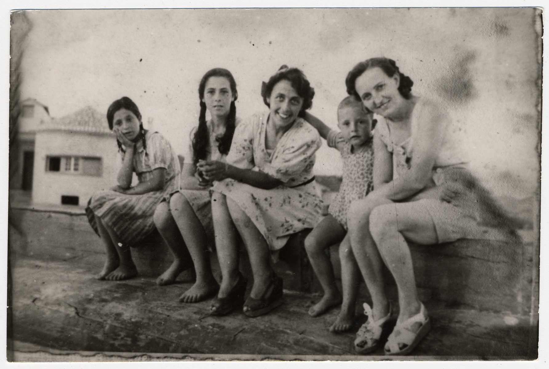 A Jewish mother and child in hiding in Albania sit on a wooden ledge together with their resucer and her family.  From left to right are unknown, Johanna Gerechter, Alice Gerechter, Luan Pilku, and Lizalotte Boetge-Pilku.