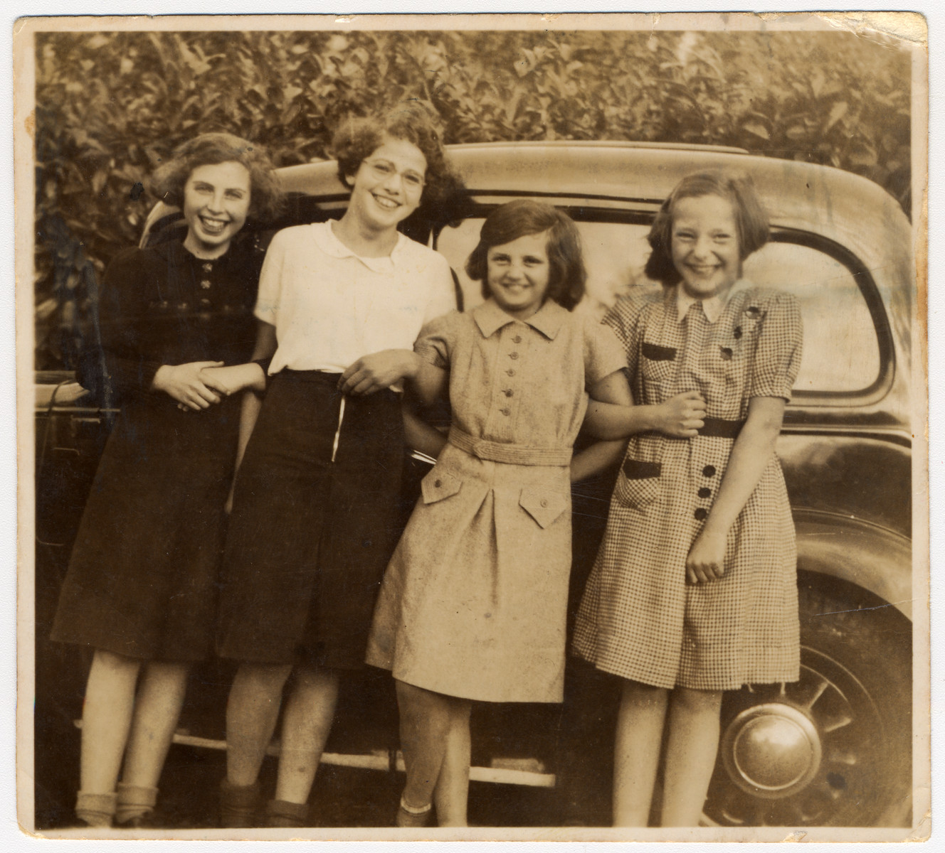 Four Jewish girls who came to England on a Kindertransport pose in front of an automobile   Pictured from the left to the right are: Sophie Goldschmidt-Stern, Ruth Adametz-Cohen and Margot Hirschi.