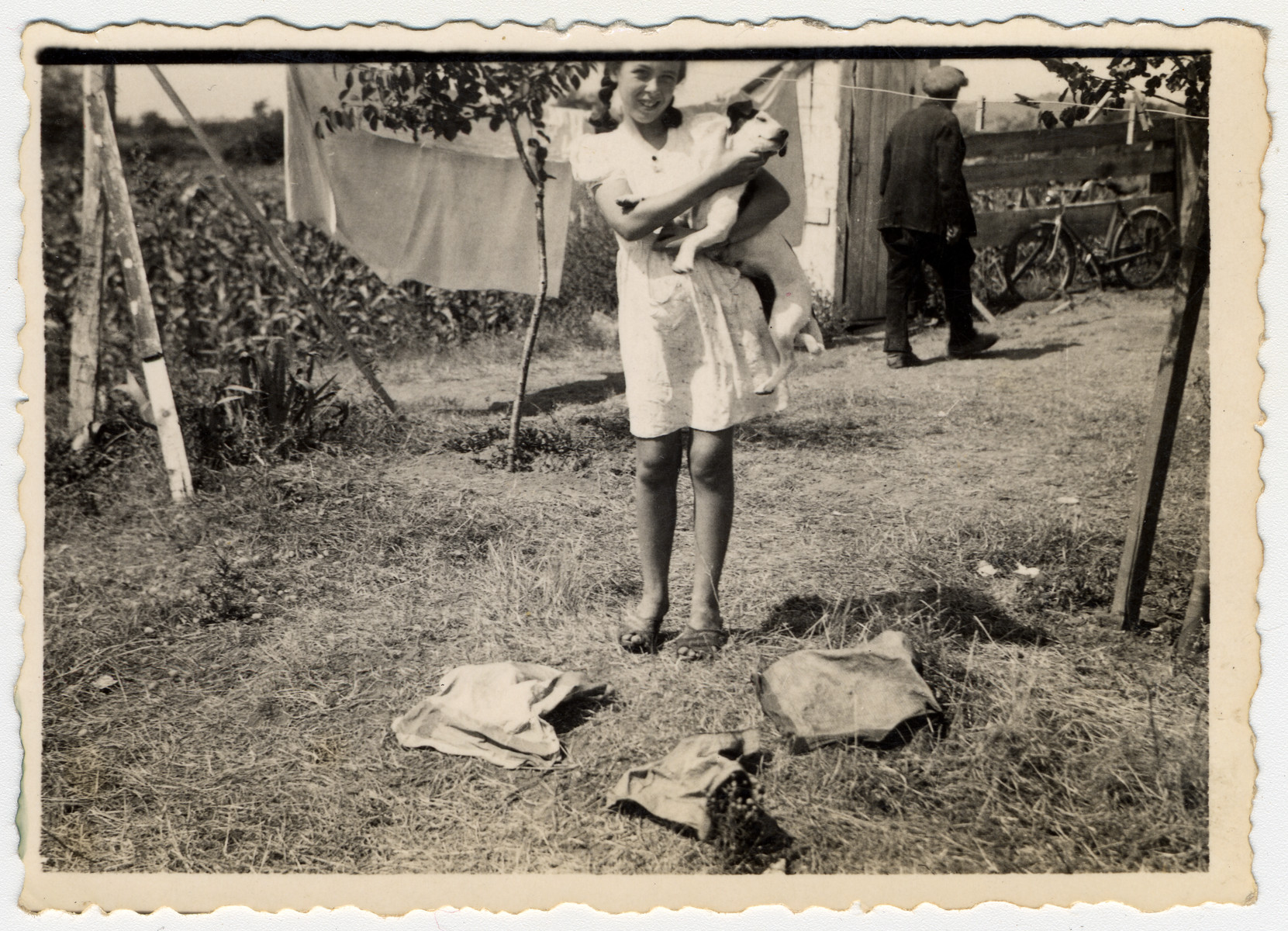 A German-Jewish refugee girl stands with her dog Piccola next to a laundry line in Albania.  Pictured is Johanna Jutta Gerechter.  Her family was supporting themselves in exile by doing laundry for Italian truck drivers.  The owner of the house is walking past in the background.