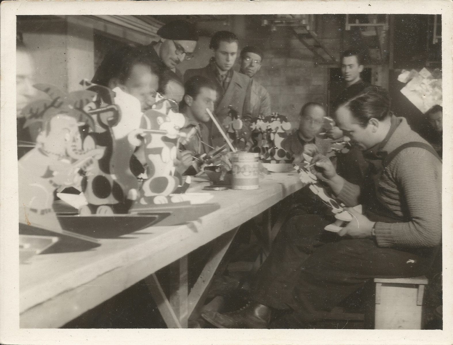 Internees decorate toys in a workshop in Les Milles.  Siegfried Lindheimer is pictured first row, right.