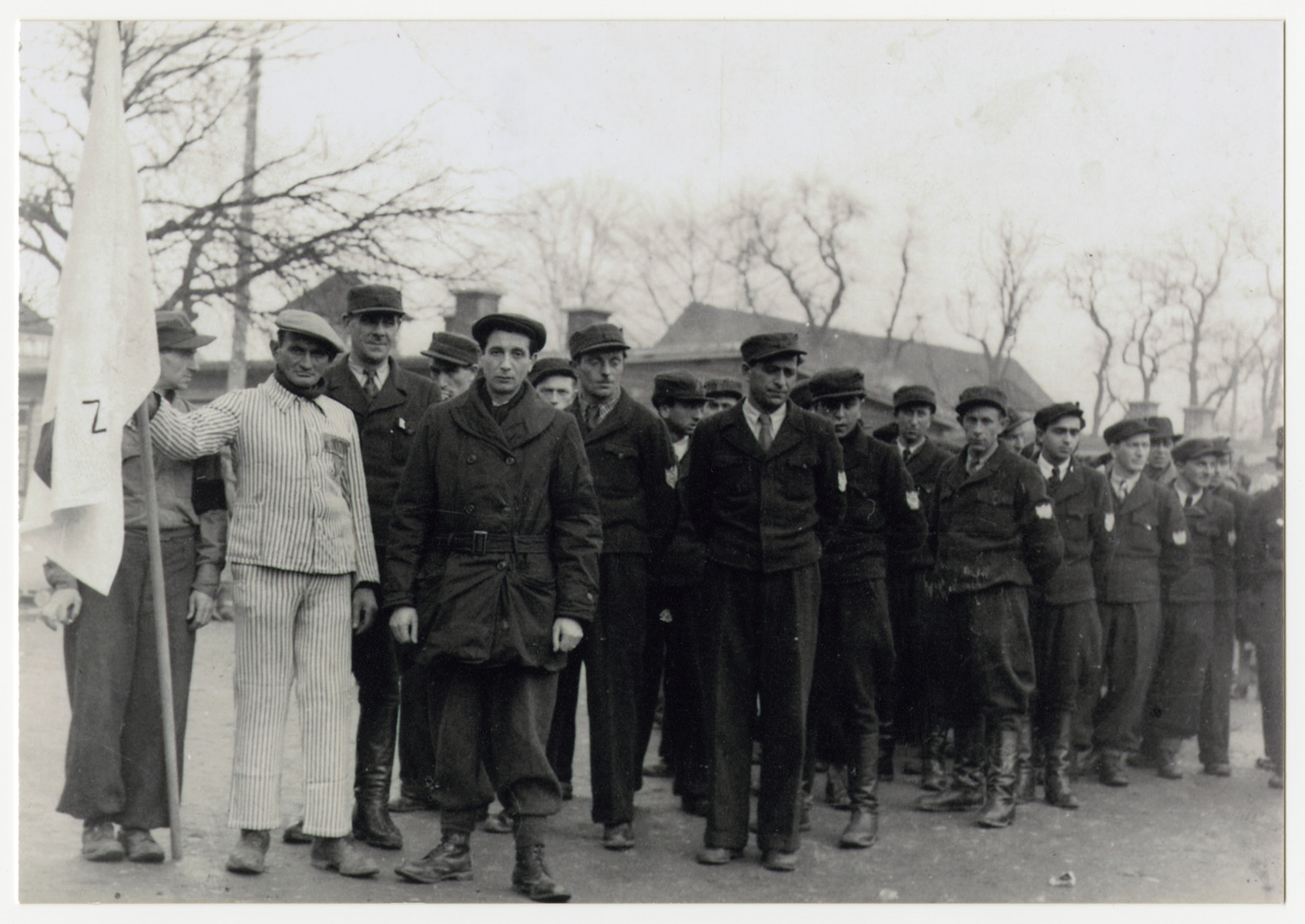Jewish police line up behind a man wearing a concentration camp uniform at a memorial event [probably in the Steyr displaced persons camp].