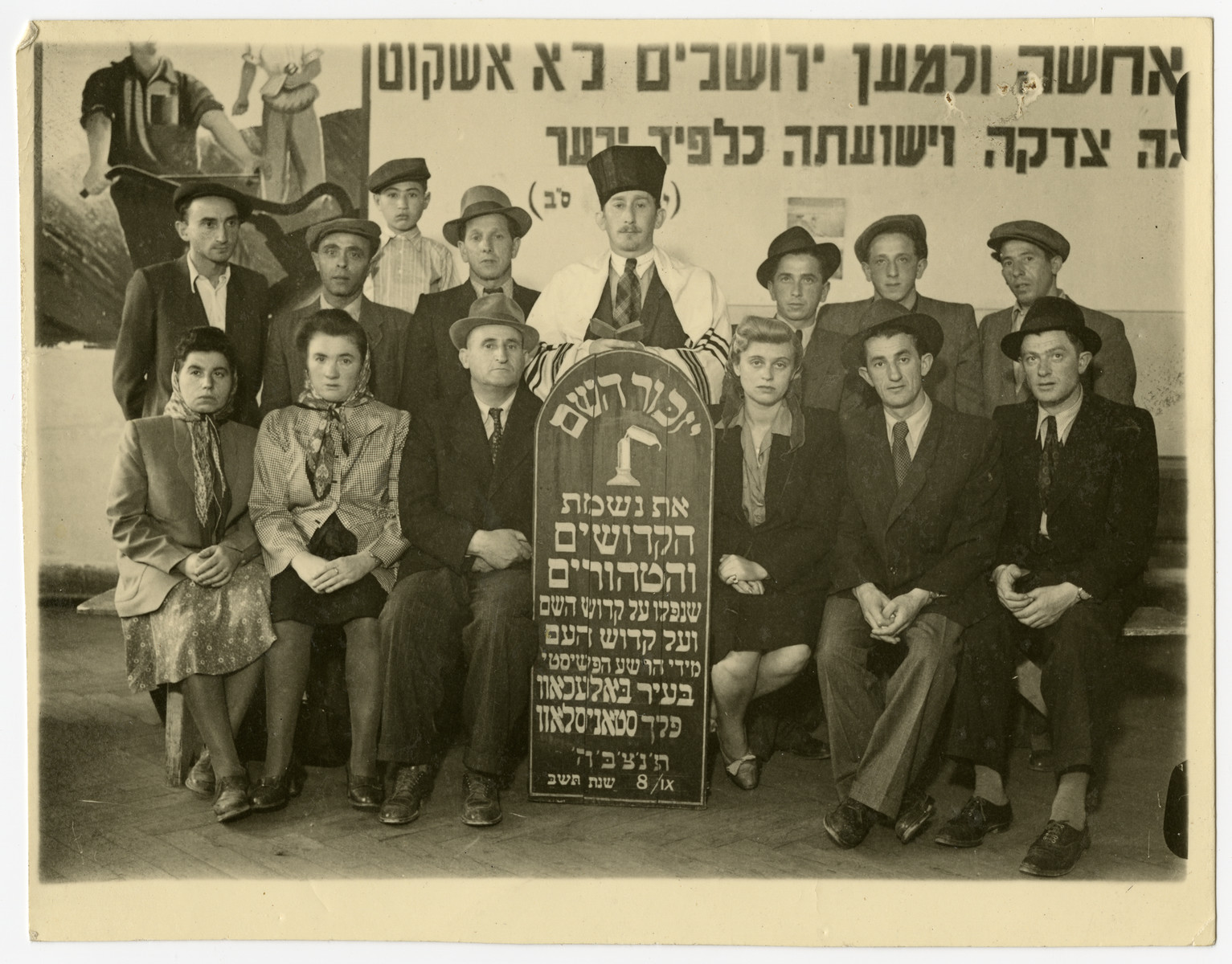 Jewish survivors from Bolechow gather for a memorial to the victims of the town.    Regina Zarwanitzer Lowensohn is seated to the right of the memorial.  To her right are brothers Avrum and Leizer who later moved to the U.S..