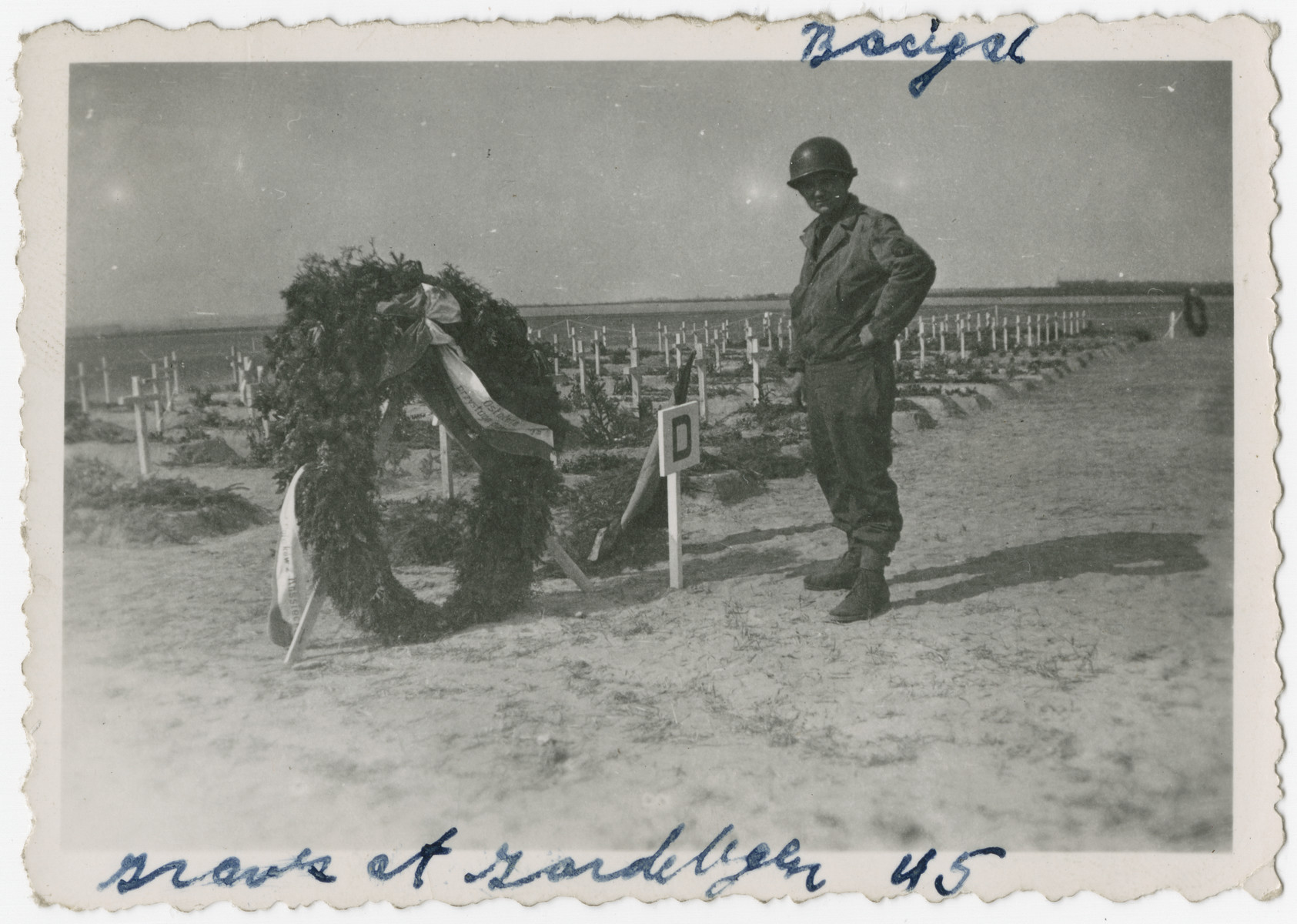 An American soldier poses next to a wreath placed by the graves of the victims of the Gardelegen atrocity.