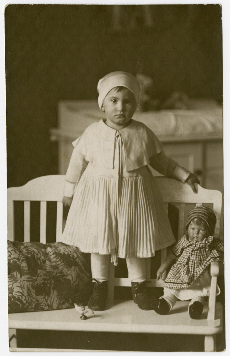 Annemarie Alexander stands on a bench next to her doll.
