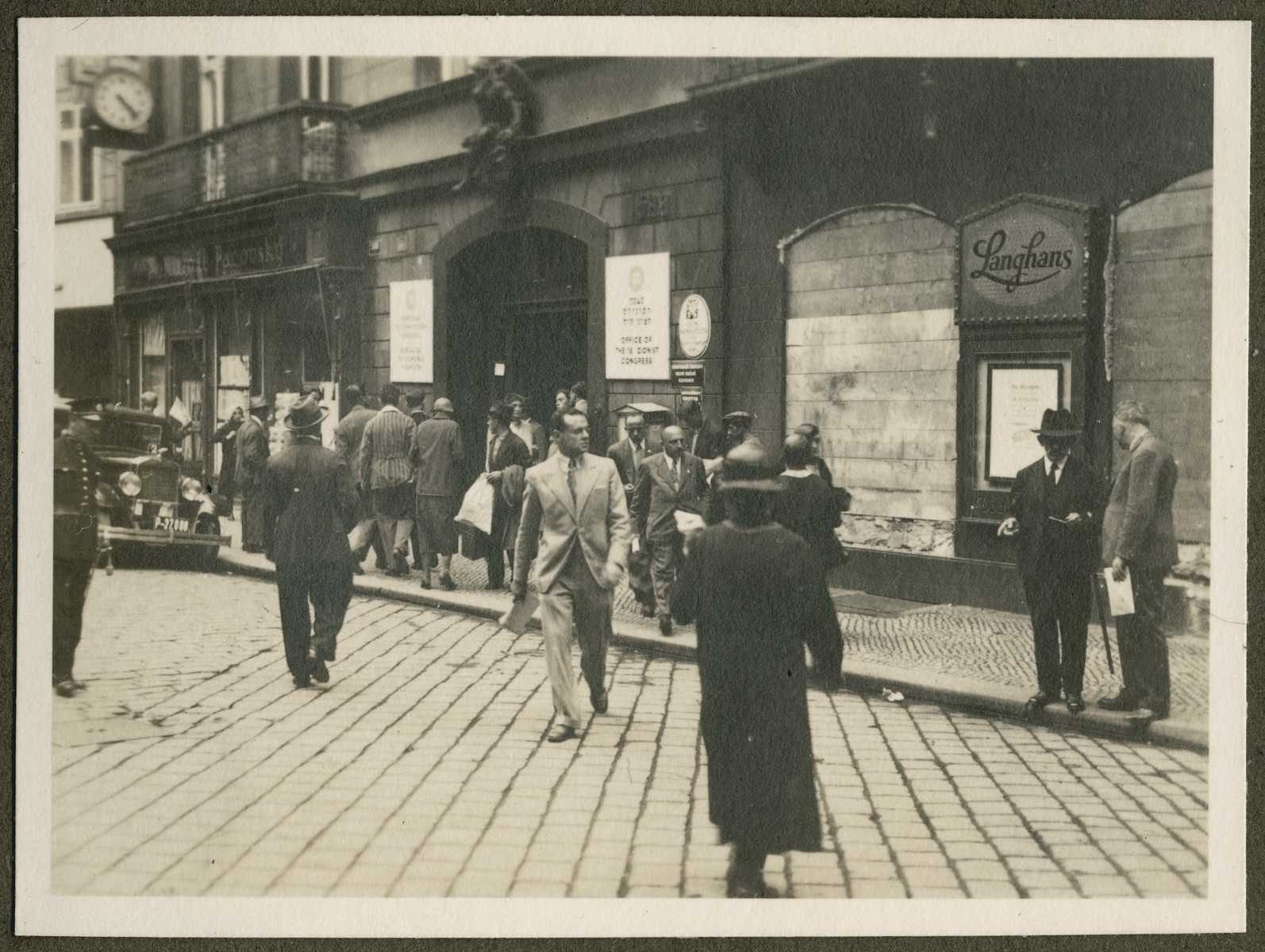 Men and women walk down a commercial street probably during the 18th Zionist Congress.