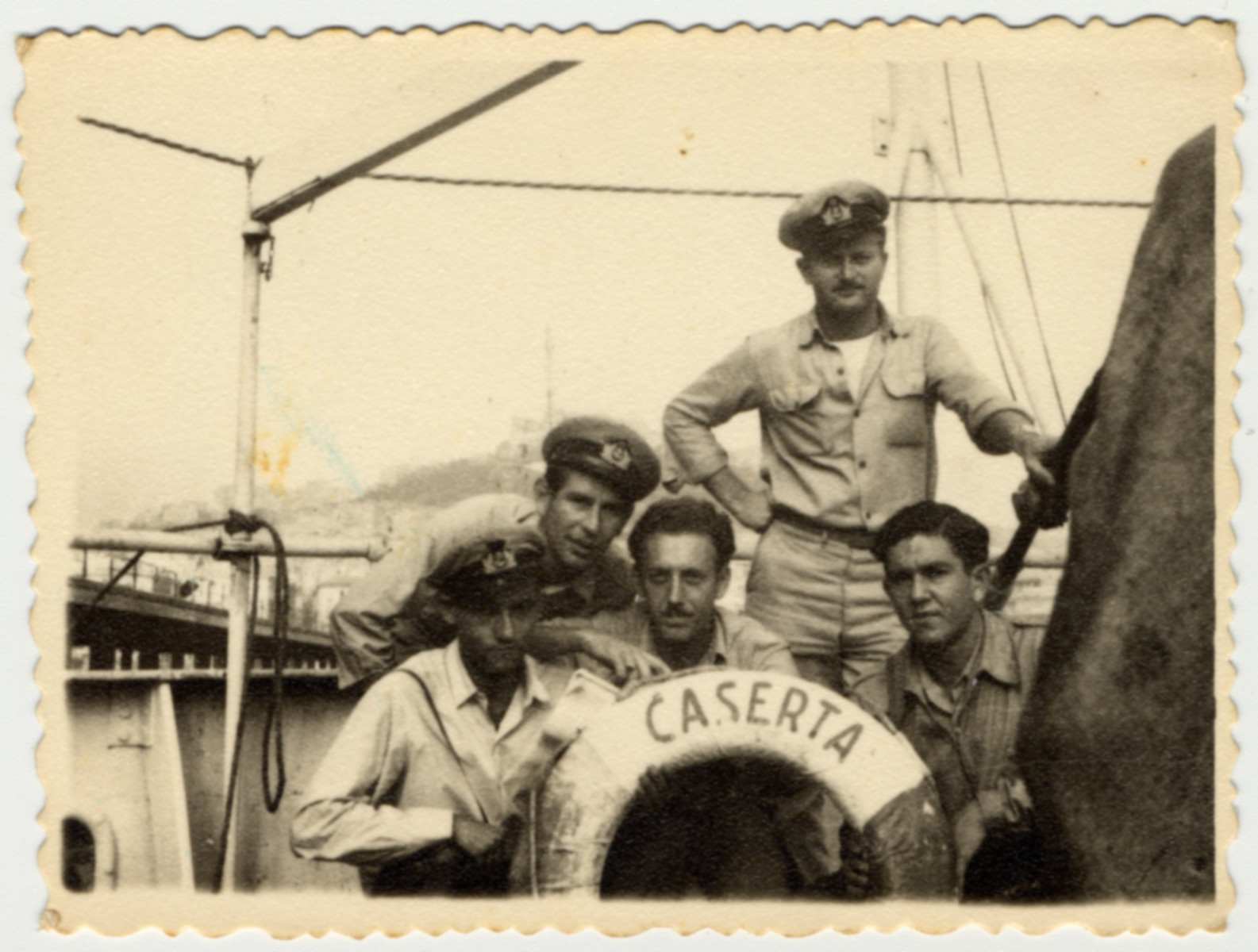 Crew members pose next to the life preserver of the Caserta.  Among those pictured are Avraham Heeres (second from left) and Teddy Rosenfeld (Vardi) center.  Teddy Vardi had helped liberate Nordhausen as a soldier in the U.S. Army before joining the crew of the Exodus and later the Pan Crescent.
