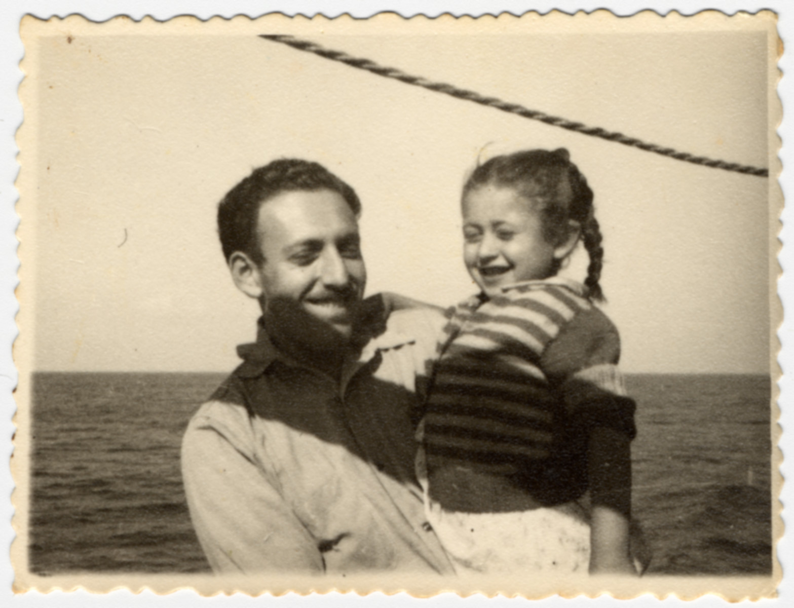 Teddy Rosenfeld (Vardi), a crew member of the Atzmaut (Pan Crescent) holds a young passenger in his arms.  Teddy Vardi had helped liberate Nordhausen as a soldier in the U.S. Army before joining the crew of the Exodus and later the Pan Crescent.