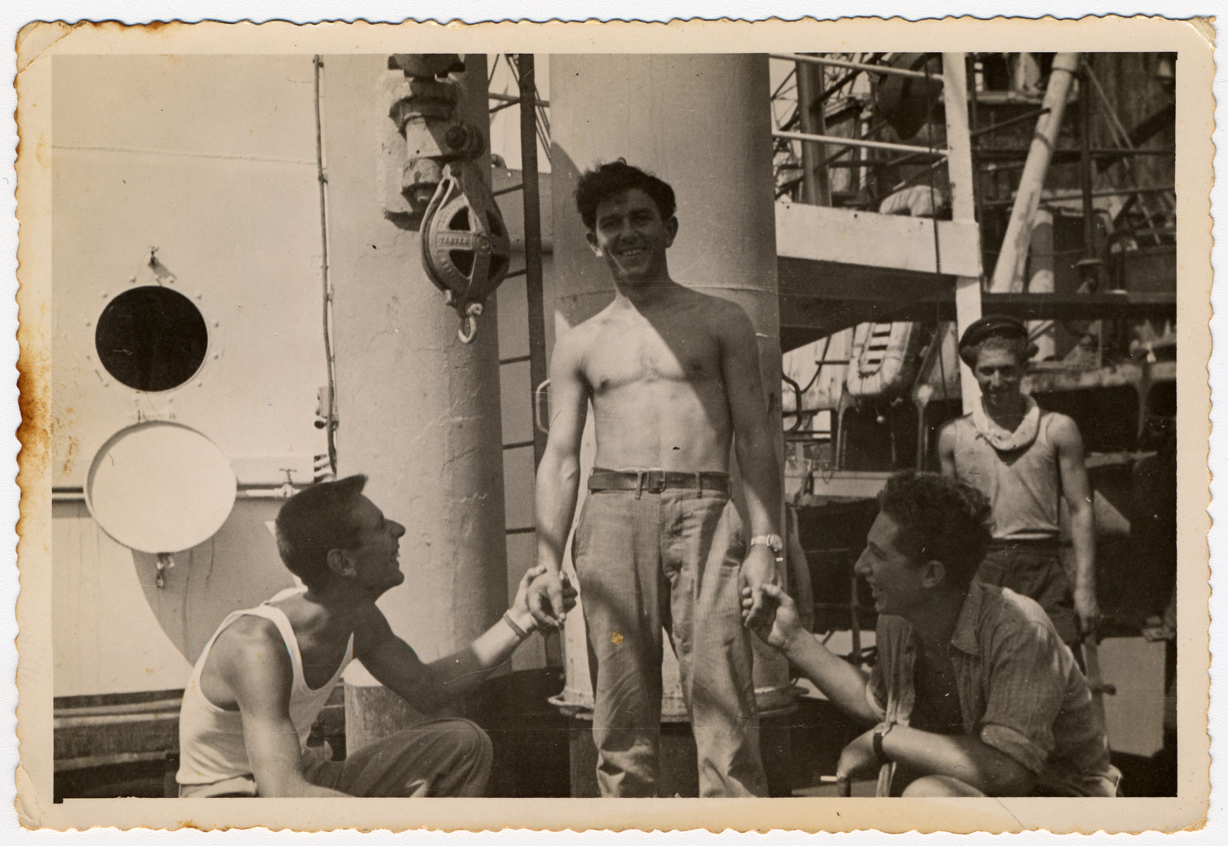 Four crew members entertain themselves en board [what is probably the Atzmaut, Pan Crescent].  Among those pictured is the captain, Ike Aronowitz (center).