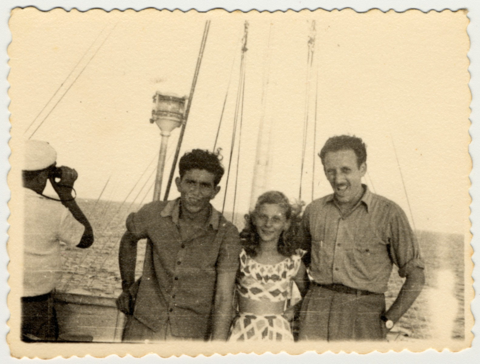 Two teenagers pose with crew member Teddy Vardi on the bridge of the SS Caserta.  Teddy Vardi had helped liberate Nordhausen as a soldier in the U.S. Army before joining the crew of the Exodus and later the Pan Crescent.