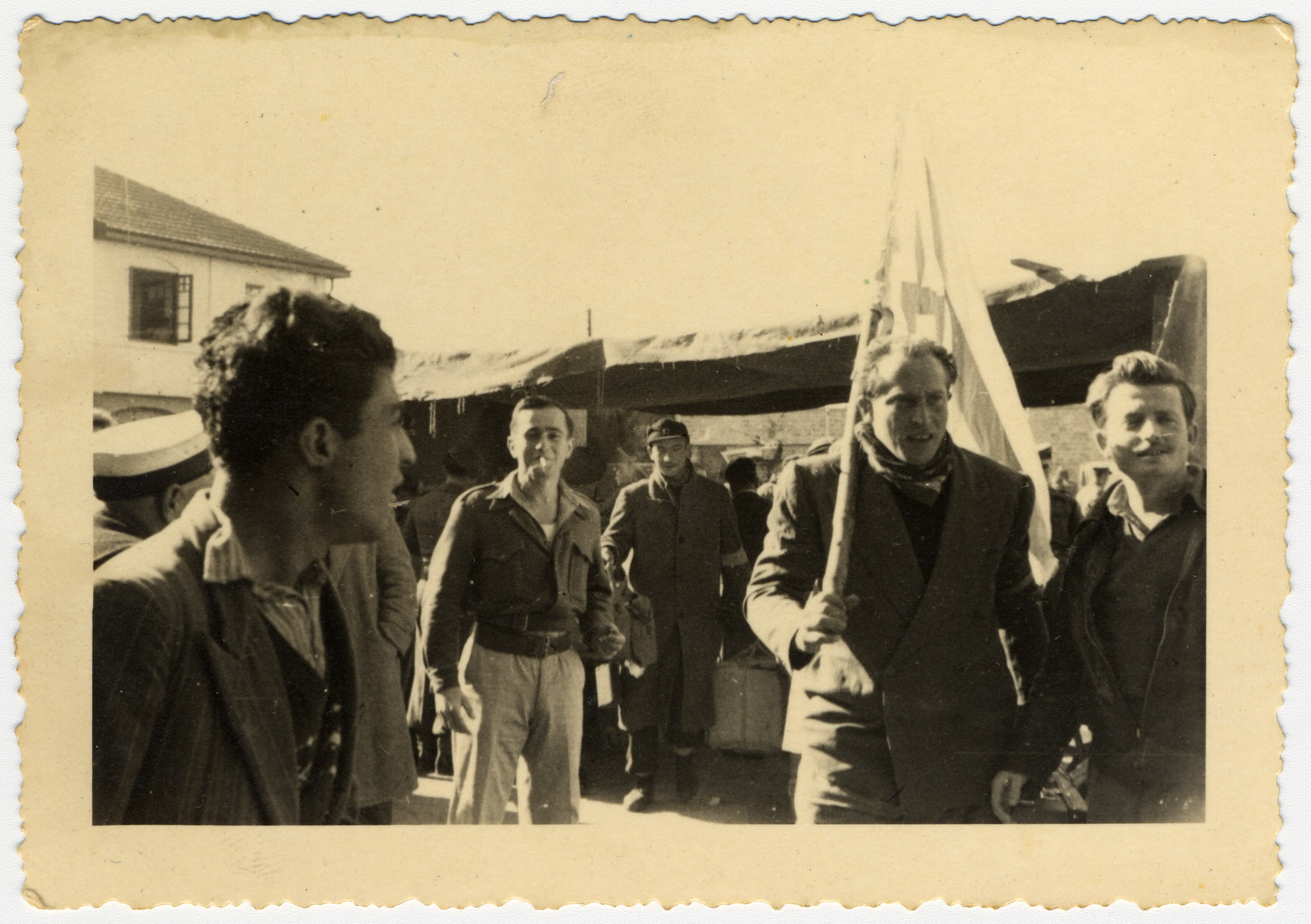 Jewish DPs gather with an Israeli flag celebrate either their arrival in Haifa or their departure from Constanta.  Pictured in the center with a cigarette is the radio operator of the Galila, Sonny Weintraub.