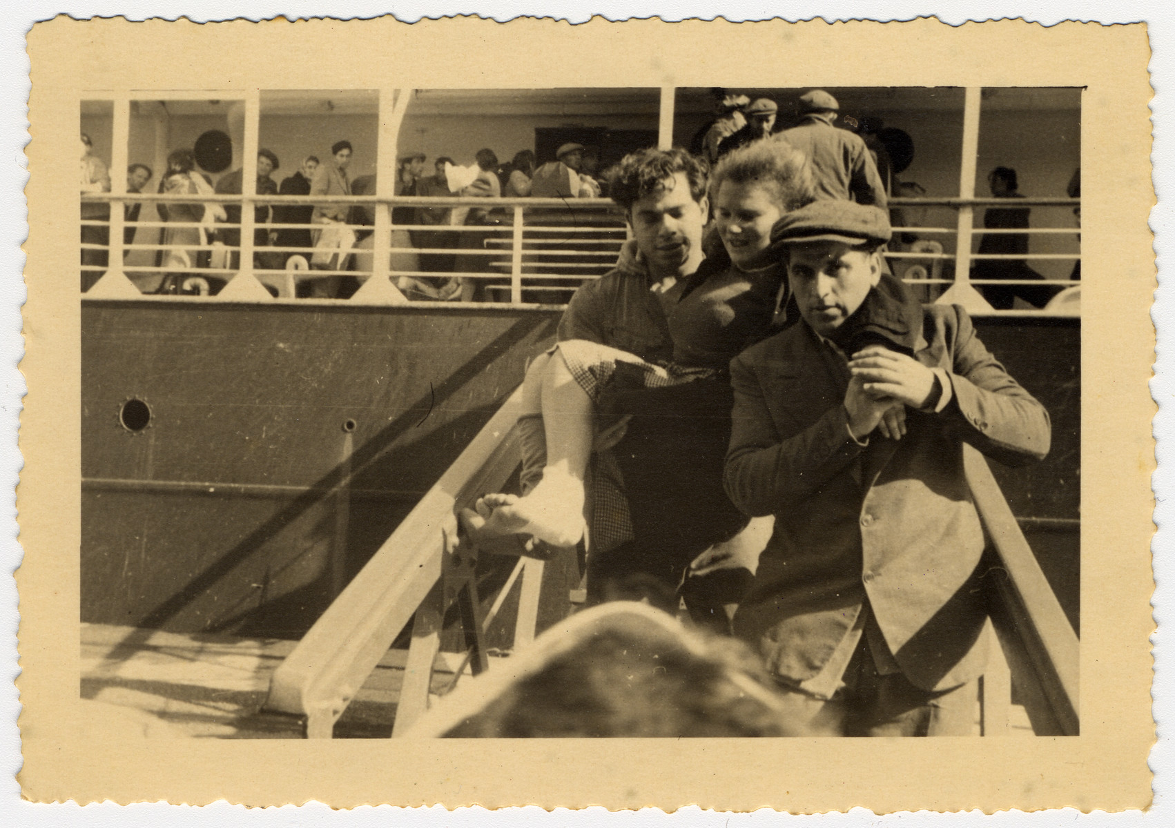 "A man carries a woman down the gangway as new immigrants arrive in the port of Haifa.  The donors caption reads ""Helping hands""."