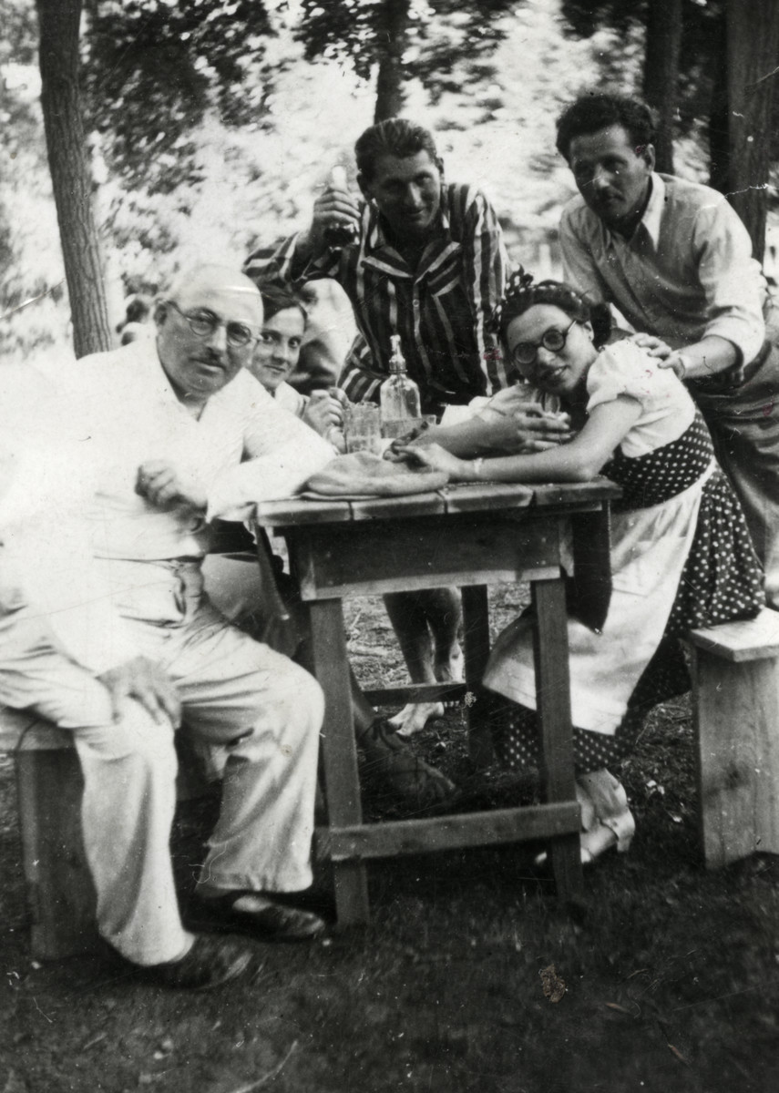 Members of the Weisz family gather for a drink in the woods.  Among those pictured are  Moshe (left), Dzusi (center), and Lili (right).