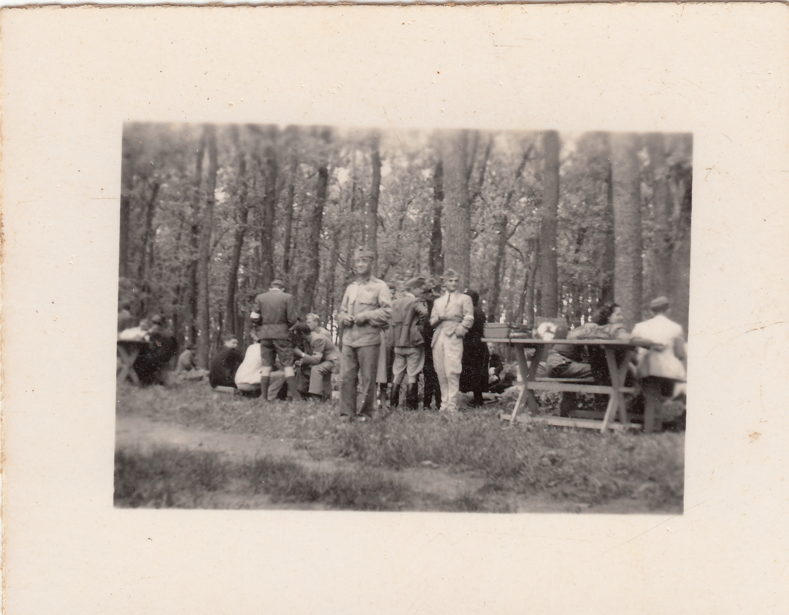 Members of a Hungarin labor battalion stop for lunch at a picnic table.  They are joined by a group of visitors.