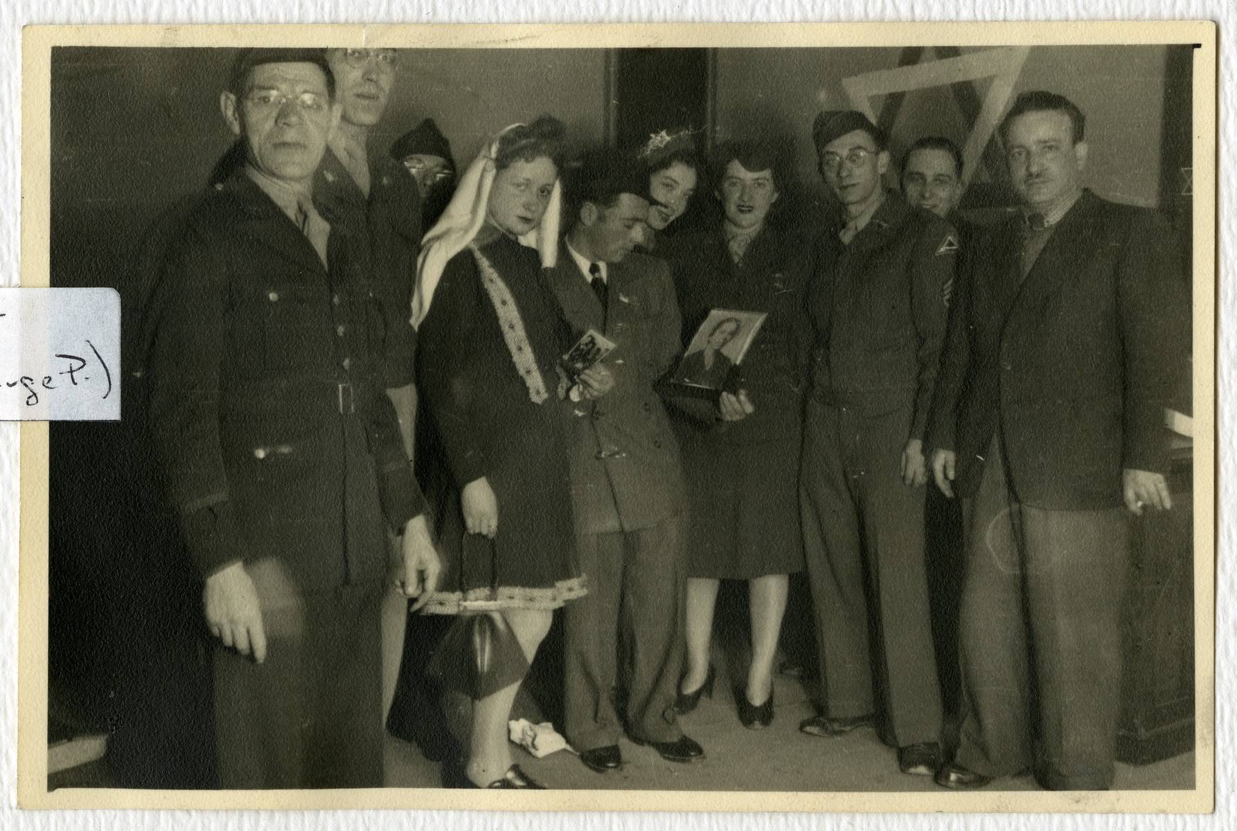Mr. and Mrs. Pressman hold the photographs of relatives who perished during their wedding in the Stuttgart dsiplaced persons camp.  Cantor Moses Rontal is standing on the far right.