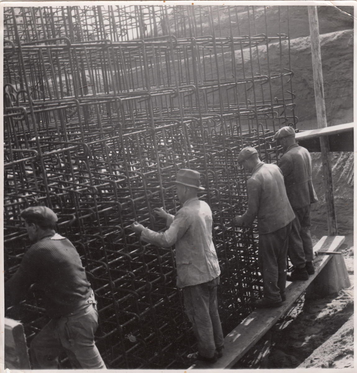 Members of a Jewish labor battalion install a metal grid at a construction site in Hajduhadhaz.