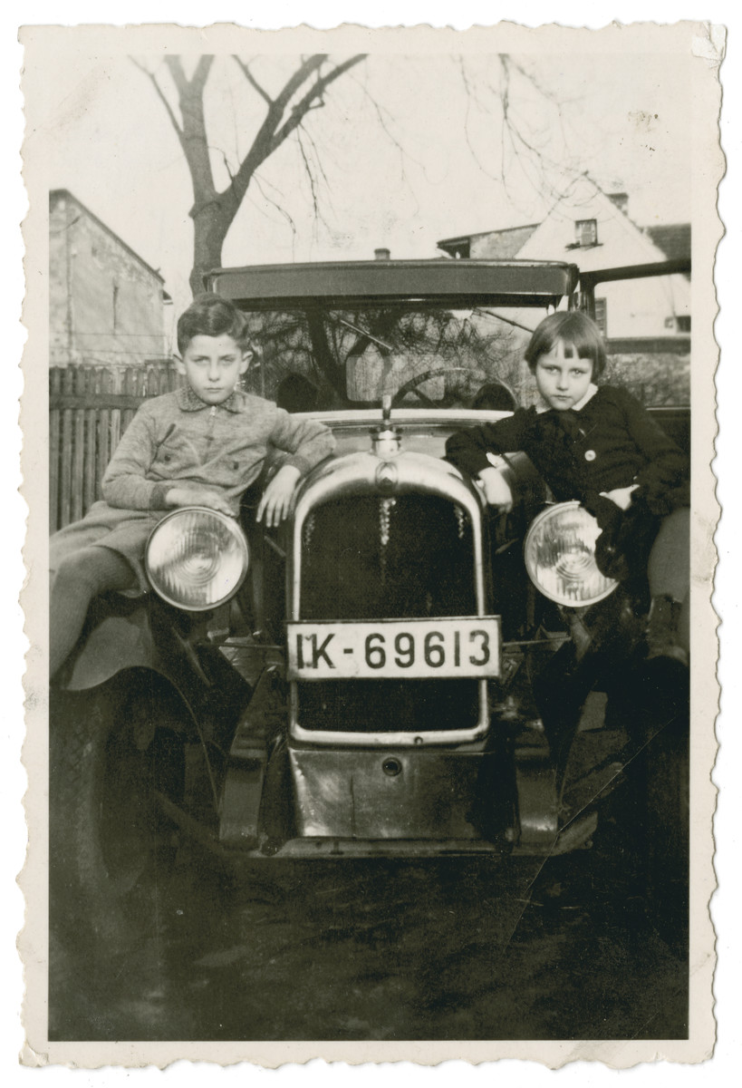Ilse Oschinksky poses with her cousin Heinz Schleyer on the running board of her uncle's car, a Limoge, in Ohlau, Germany.
