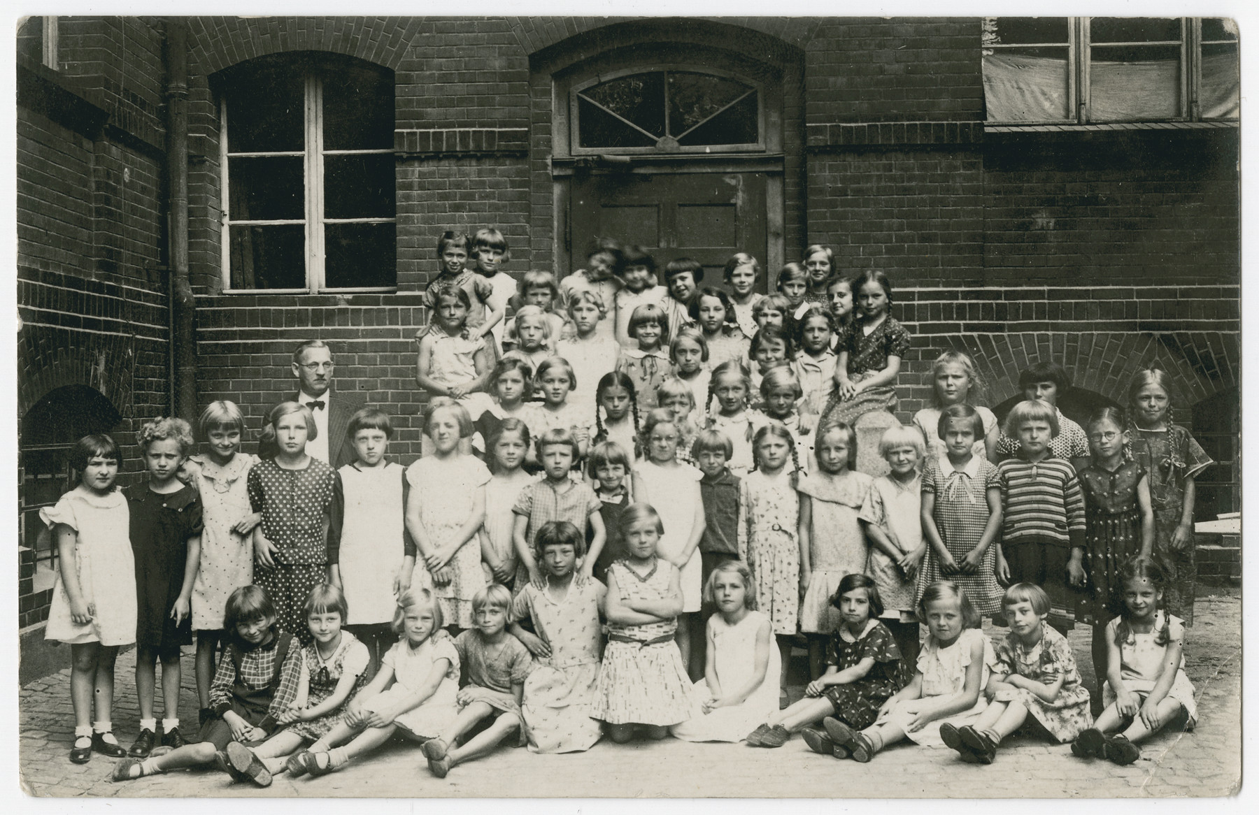 Group portrait of school girls in the Leobschuetz elementary school.            Among those pictured is Ilse Oschinsky (second from left in front row).  The teacher is Karl Teichmann.