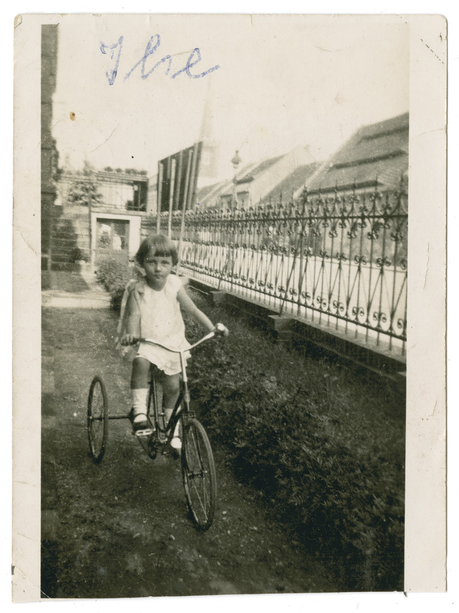 Ilse Oschinsky rides her tricycle in front of their house in Grottkay, Schlesien, Germany.