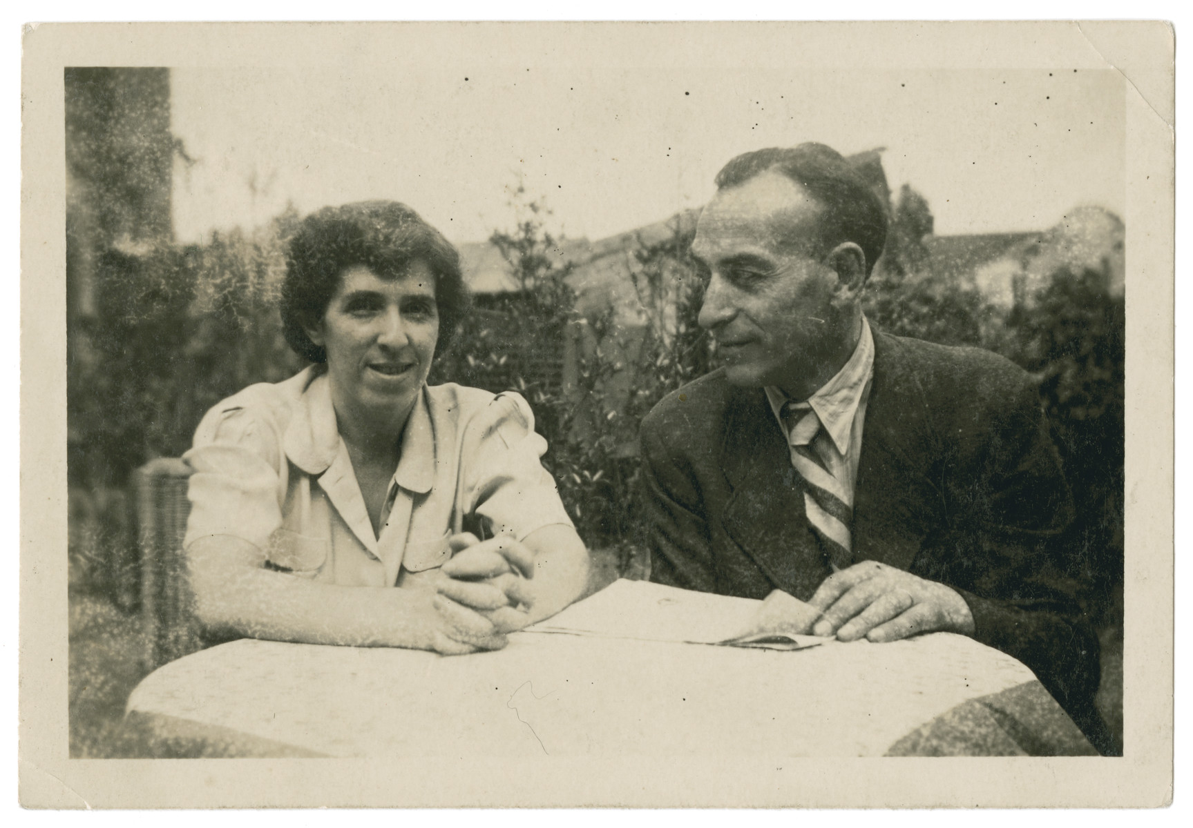 Jewish refugees Max and Erna (nee Weissblum) Pikarski (aunt and uncle of the donor) sit at an outside table in Shanghai.  They formerly lived in Neurode, Schlesien.  After the war both came to Oakland, California with many members of their family who had fled Germany to Shanghai.