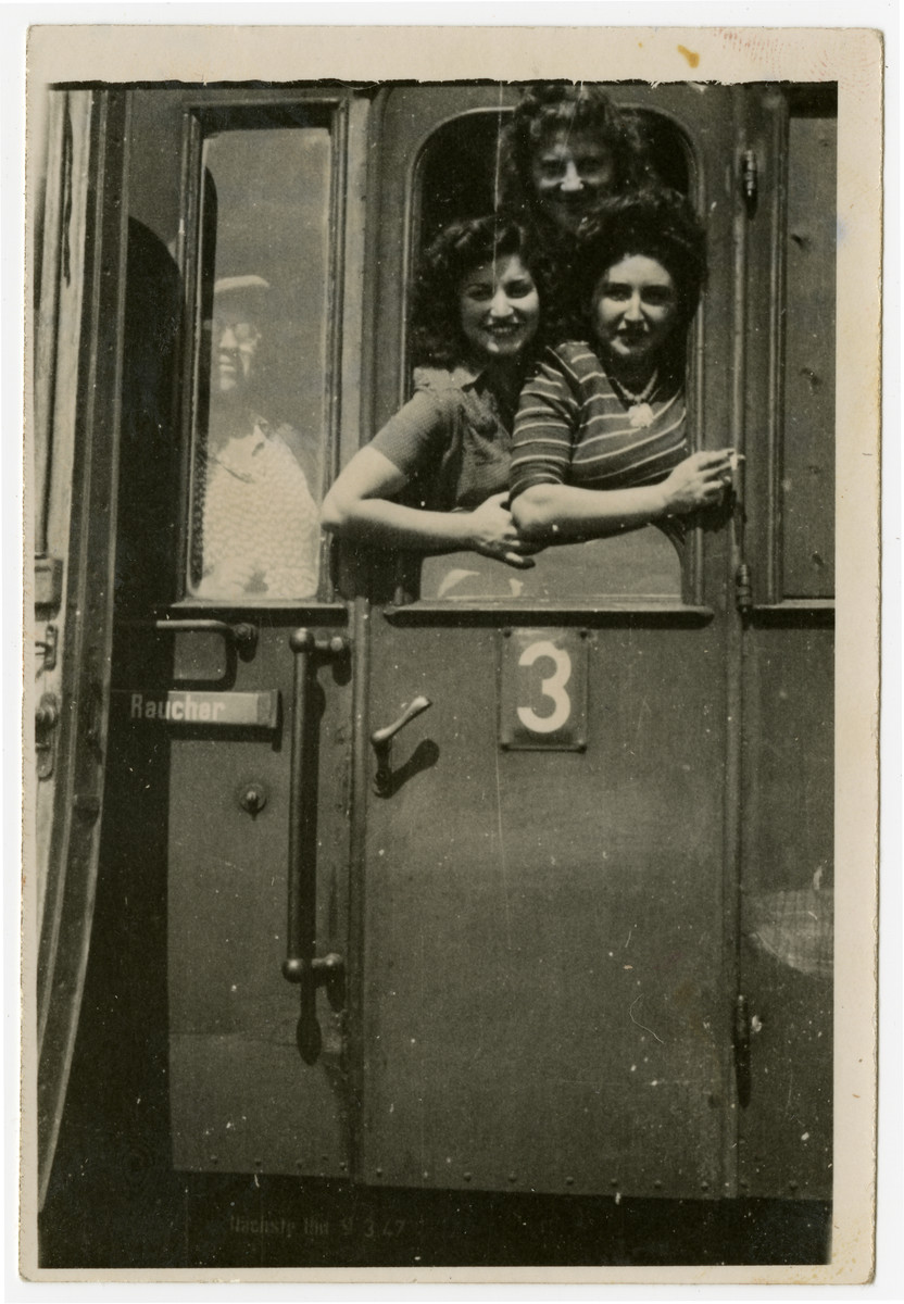 Magda and Gloria Herskovits, and their friend Muschca pose in the window of a train as they leave for America.