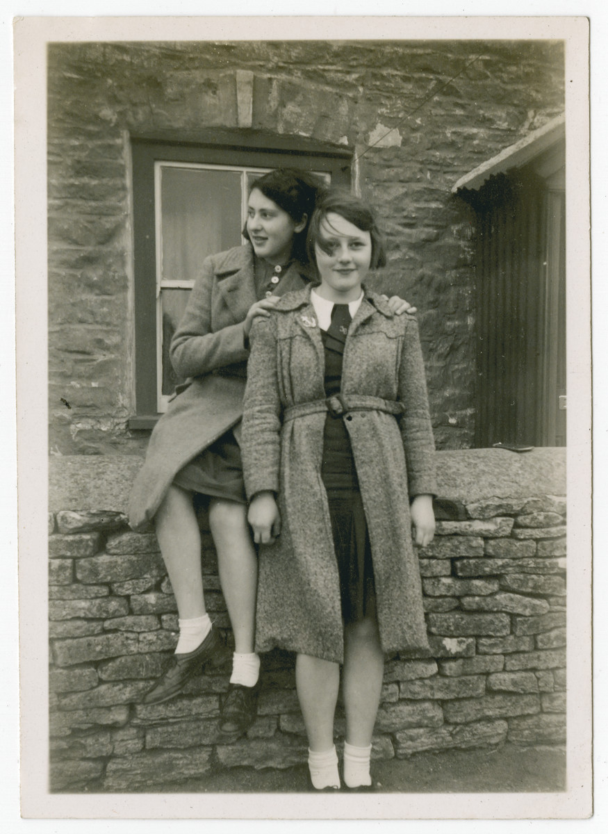 Close-up of two teenage girls who came to England on a Kindertransport.             Ilse Oschinsky is standing on the right of her friend Susie Vogel from Berlin (who later married Len Lister and became an English lady) in  front of the house belonging to Mrs. Stinchcombe with whom Ilse lived while evacuated by British Government to Hawkesbury Upton in Gloucestershire in Sept. 1939.