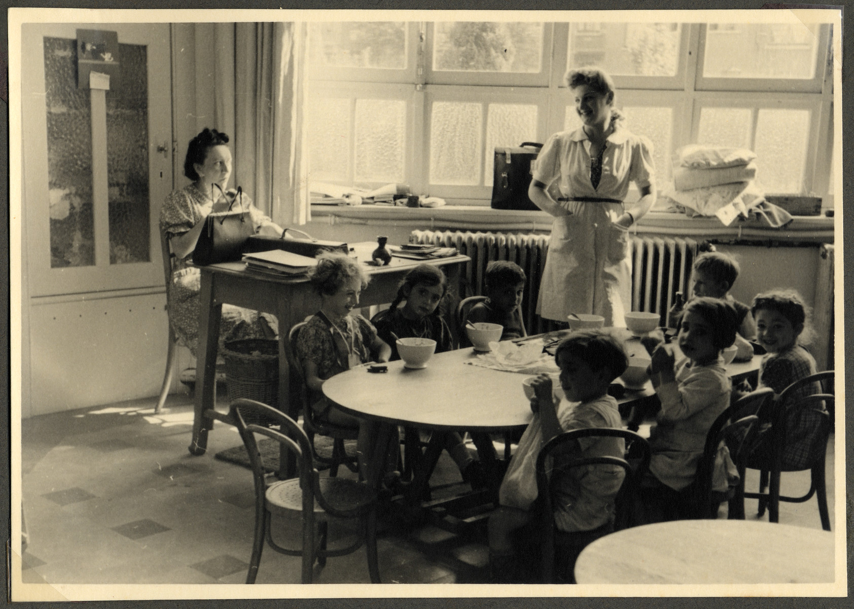 Jewish children in the Nos Petits kindergarten sit around a table to eat their lunch.  Jeanne Daman, a teacher, is standing in the center.