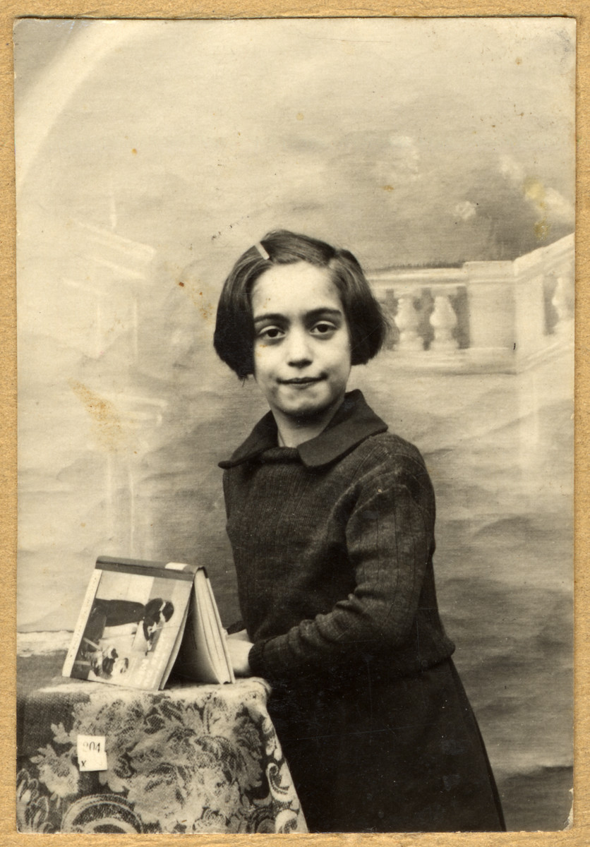 Studio portrait of Paulette Feiler standing next to a table in school, rue Beliard Paris 18, with a book she received as a first prize for the best student of the year 1939.