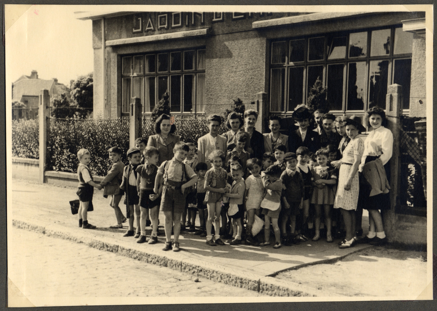 Group portrait of children and teachers in the Nos Petits children's home.  Jewish staff members are wearing a Star of David.