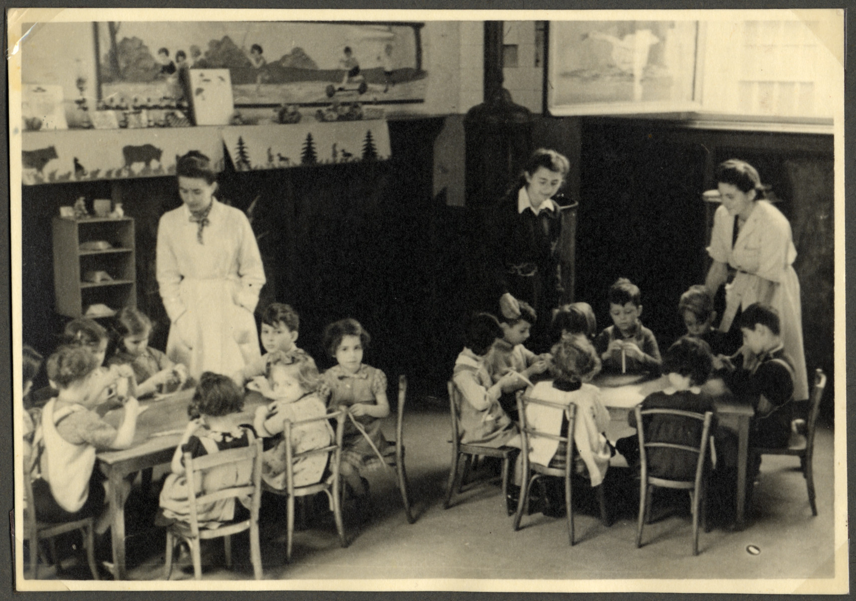 Children sit at tables to do an art project in a classroom in the Nos Petits Jewish kindergarten.  The teacher in the center is wearing a Star of David.
