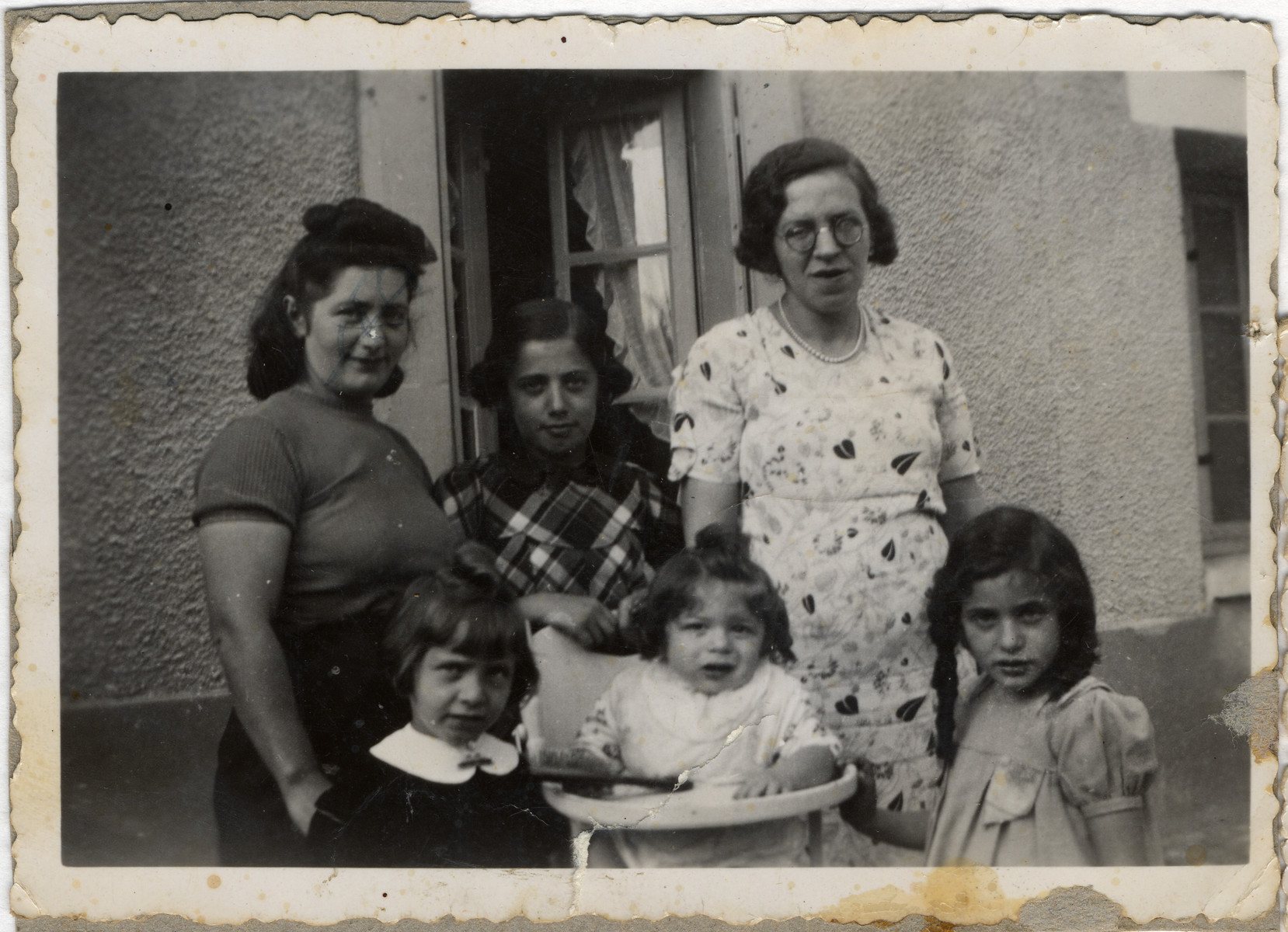 Group portrait of an extended Jewish family taken in front of the house of Jacques Gimelstein  in Mesnil Esnard.  Pictured from left to right, Rachel Suganas Gimelstein (aunt of the donors), her daughter Paulette Gimelstein, and Rachel Gimelstein Feiler.  Below are Solange Gimelstein, Michel Feiler, and Annette Gimelstein.