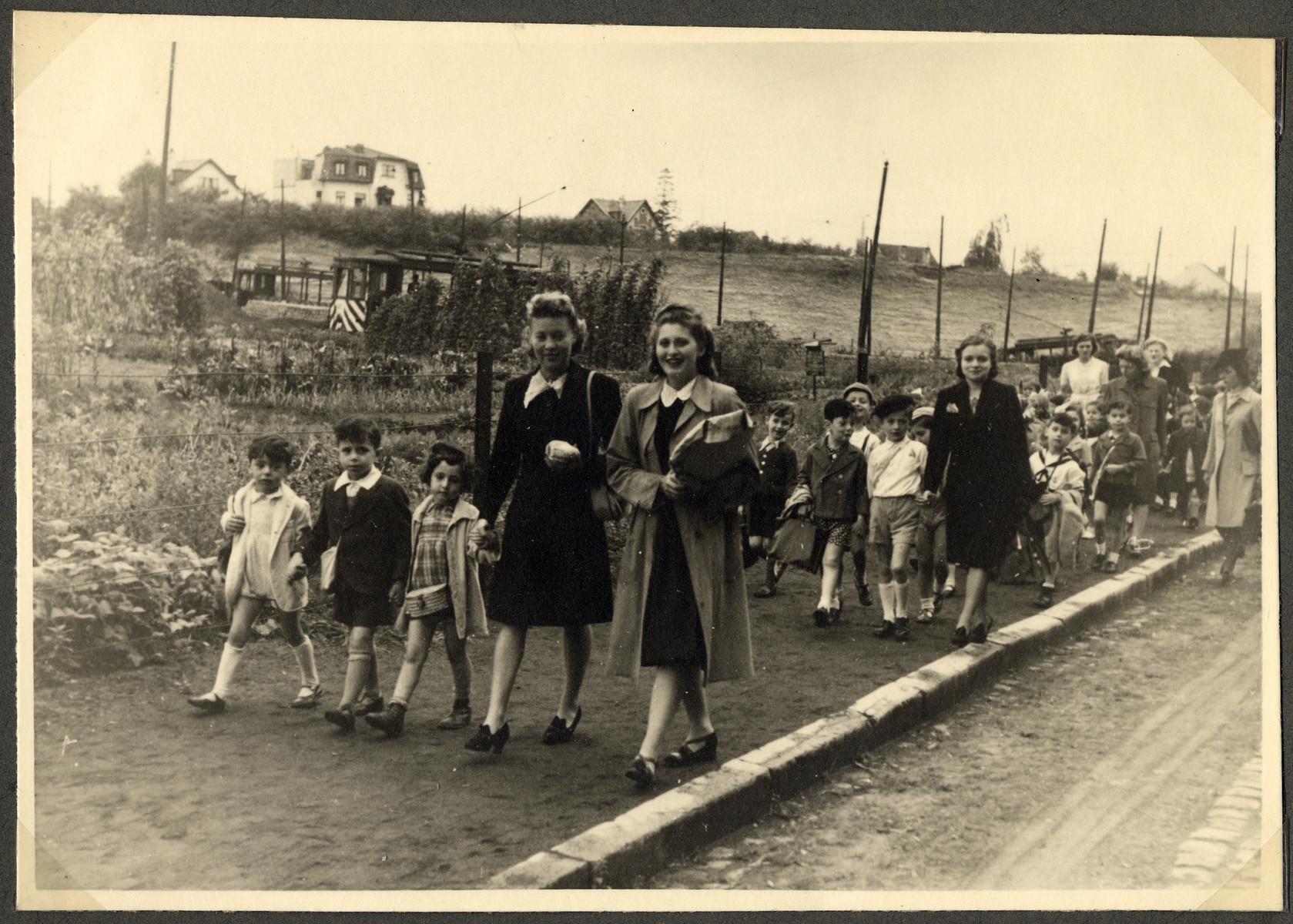 Teachers escort children from the Nos Petits Jewish kindergarten on an excursion.