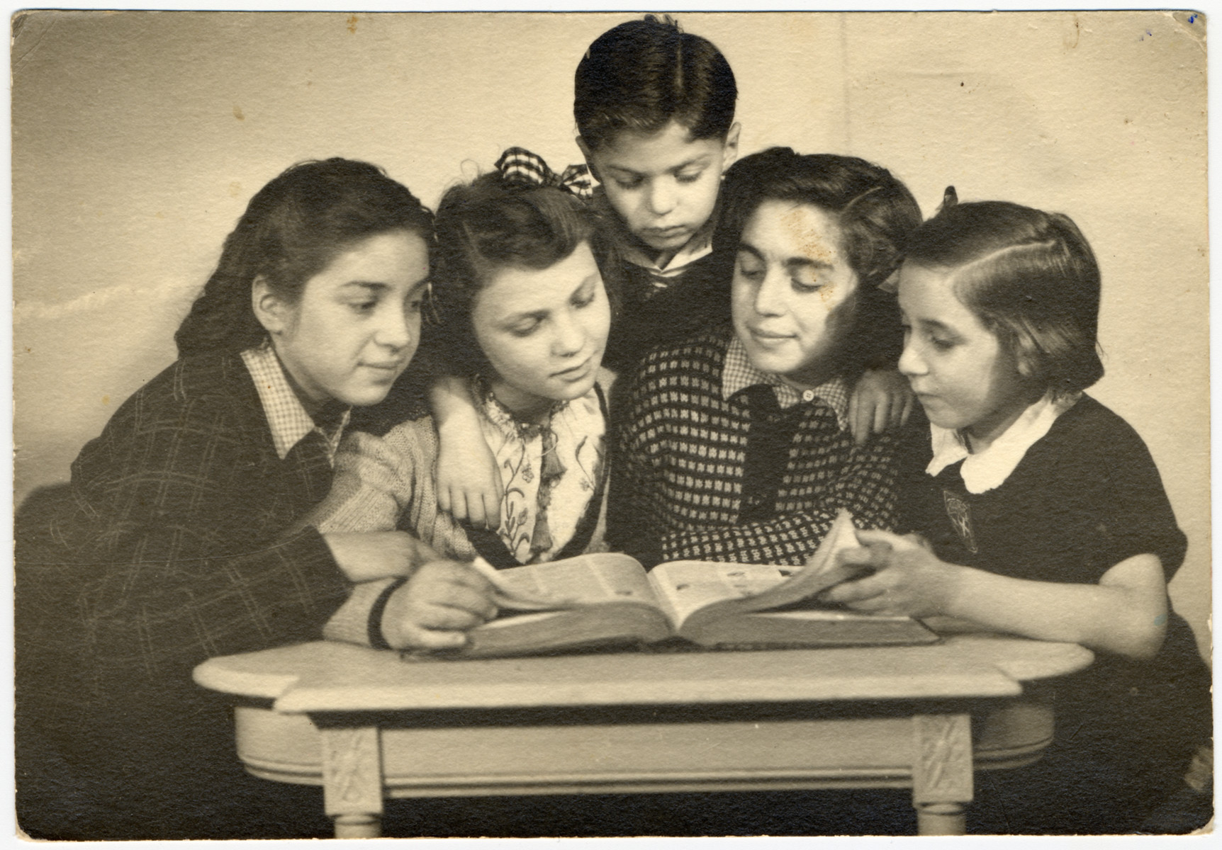 The Feiler children study a book together after their return to Paris from a Jewish orphanage in Andresy.  Pictured are Dora (Denise), Gisele, Michel Feiler, Paulette Feiler and Jacqueline Chessman.