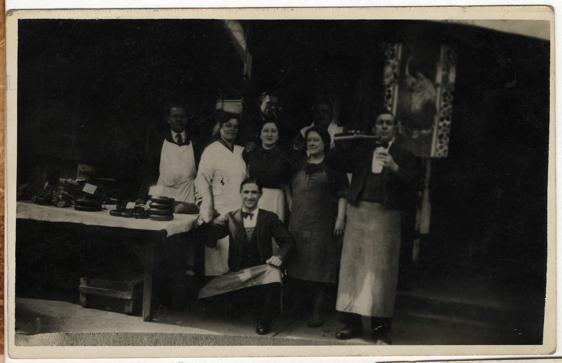 The staff of Albert Abramowitch's cafe poses next to a display of food outside the cafe.  The second woman on the right is his wife, Henriette.  Albert Abramowitch was the older brother of Roche Leja Gimelstein.  He switched his name to escape the Russian army and kept his pseudonym throughout his life.