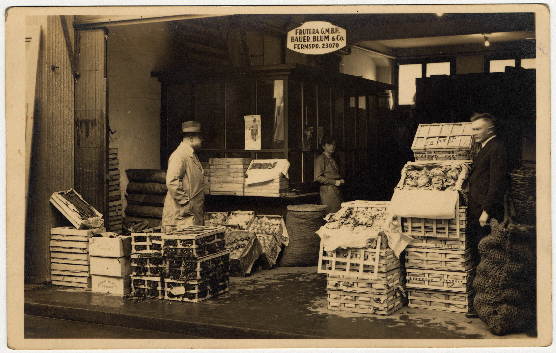Two men and a woman work instide the Bauer, Blum and Co. Frutera amid crates of fruit and vegetables.