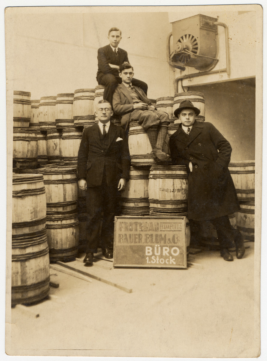Four German-Jewish men pose next to wooden  barrels in the Bauer, Blum & Co. Frutera.