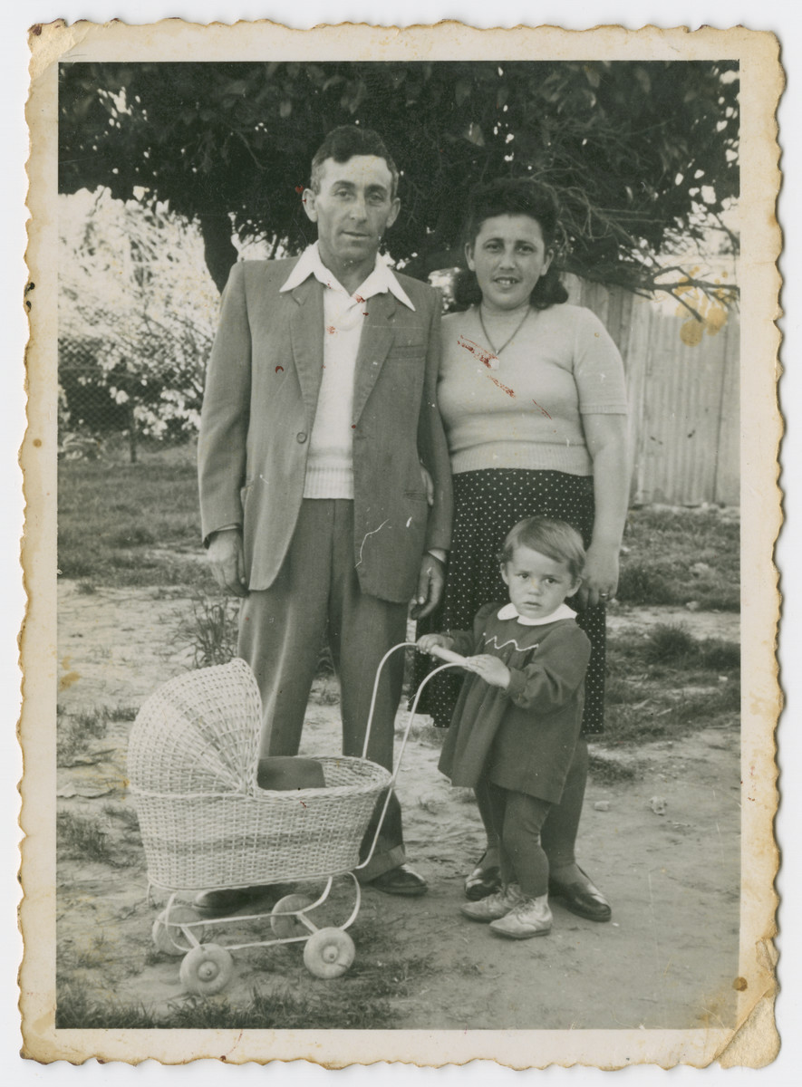 The Lanzer family poses outside shortly after arriving in Palestine.  Pictured are Szyje, Alta and Yocheweth Lanzer who is pushing a doll carriage.